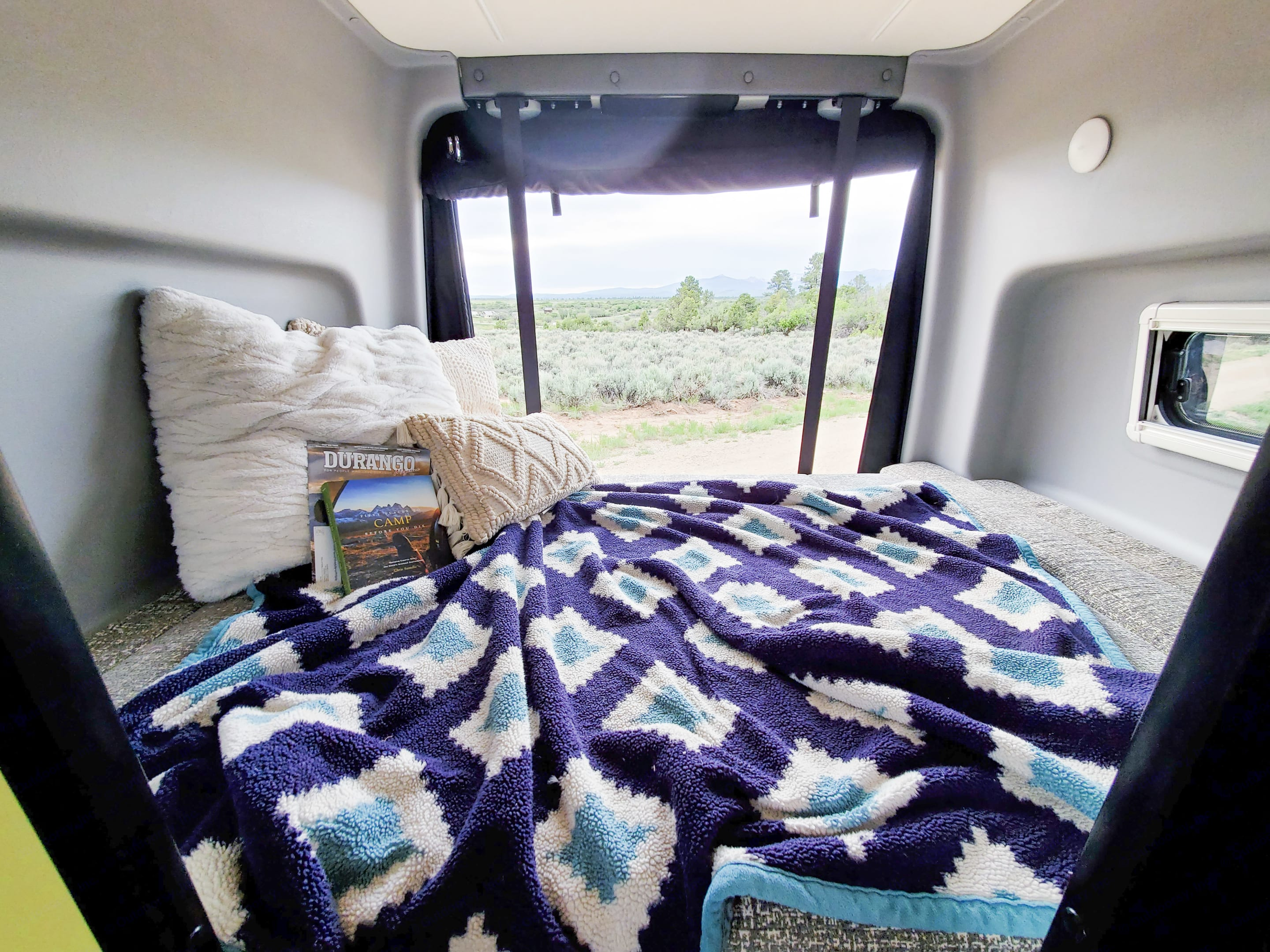 Cozy and spacious queen sized bed in the back.  Open the back doors to enjoy the views. . Winnebago Revel 2020