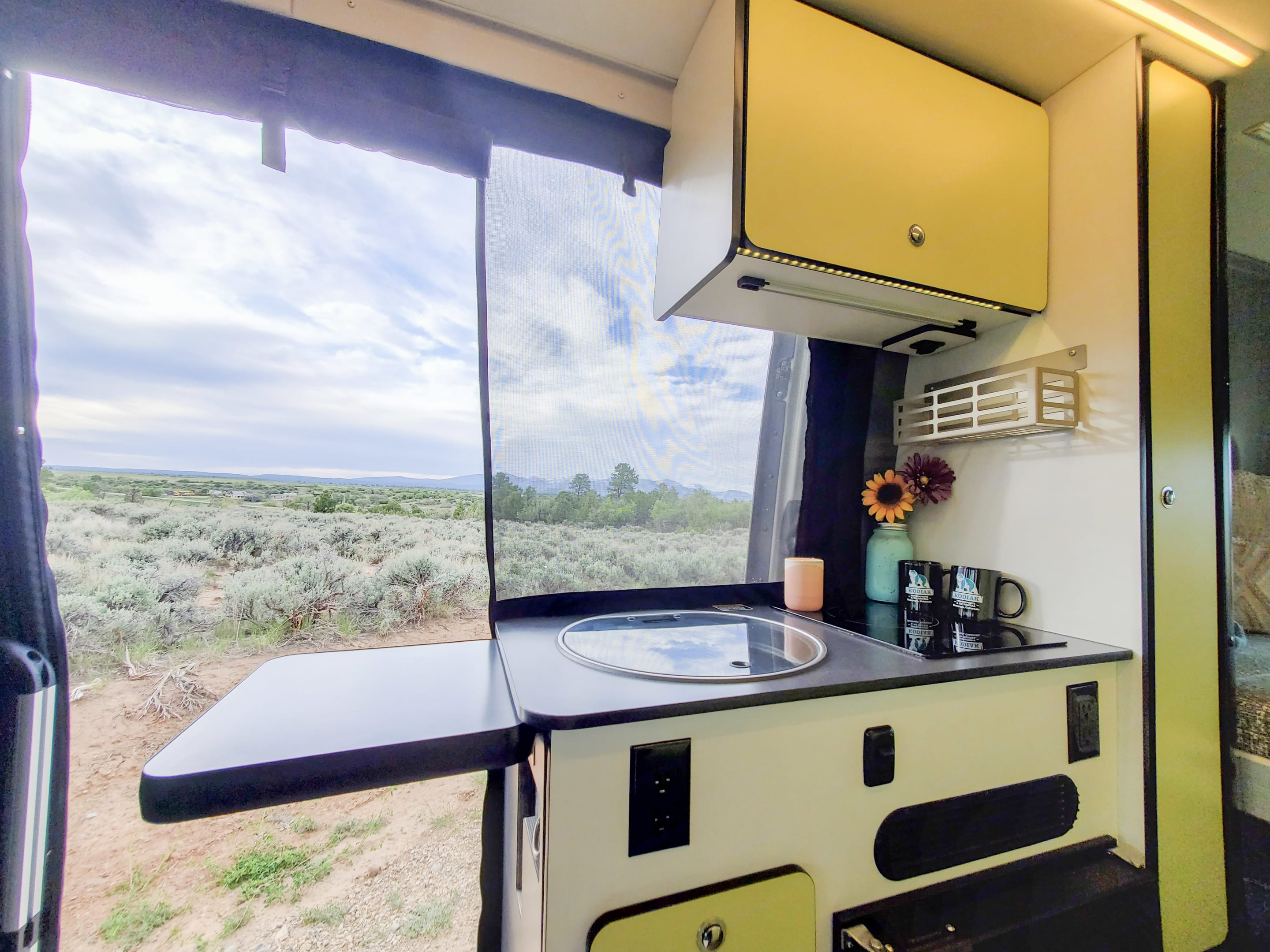 Kitchen area with sink, stove, and refrigerator. . Winnebago Revel 2020