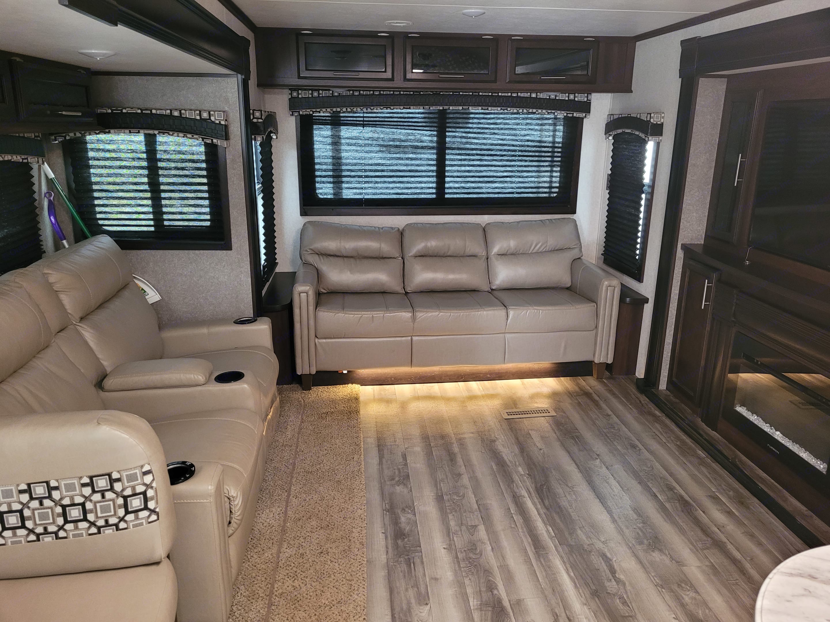 Living room with reclining chairs, sofa converts into full size bed, big screen TV, sound system, electric fireplace. Jayco Jay Flight 2019