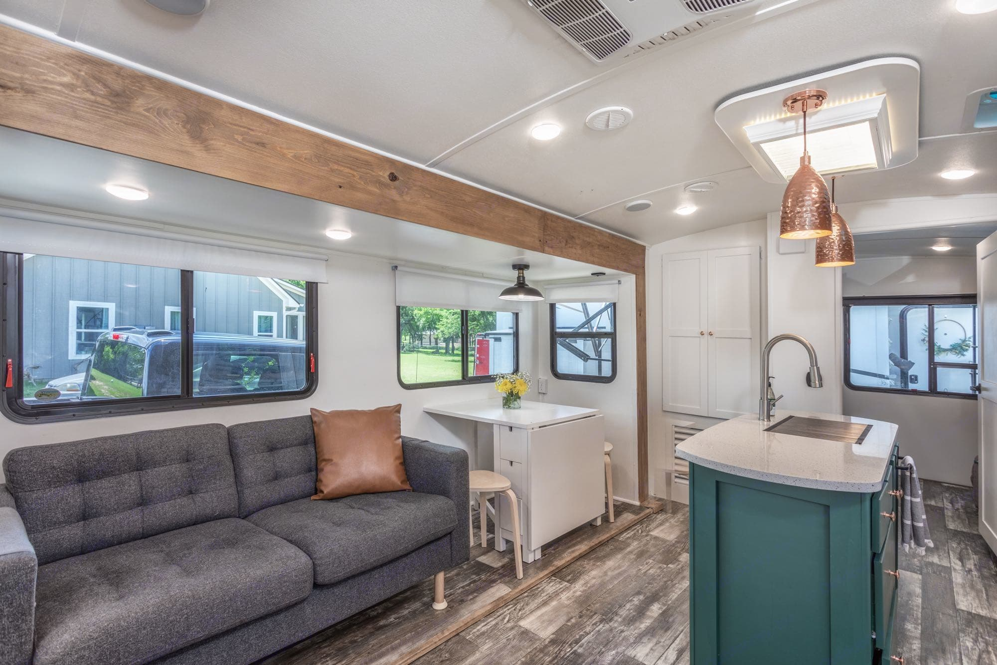 couch across from roll down tv, dining table with fold out table, 4 stools (2 chairs stored under couch for extra seating), cabinet with extra pillows, blankets and sheets for extra bed in bunkhouse; as well as extra tools as needed.. Keystone Outback 2019