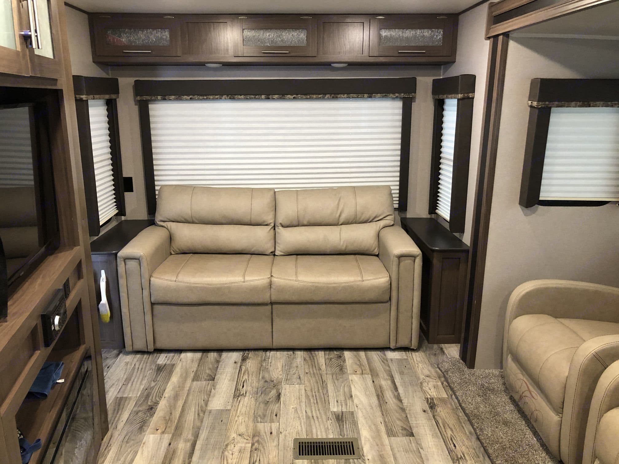 Tri-Fold Sofa with huge picture window behind it.  TV in entertainment center swings out to be viewed from the sofa.. Keystone Hideout 27RLS 2020