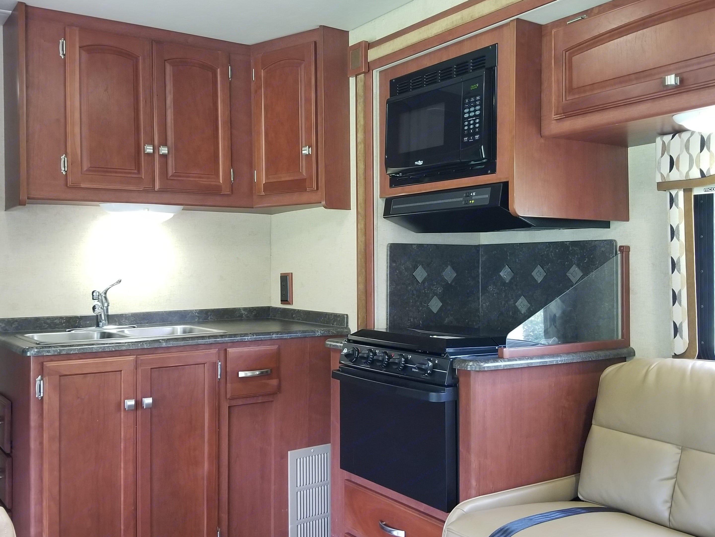 Kitchen area, stove, oven, sink, microwave. Winnebago Access 2012