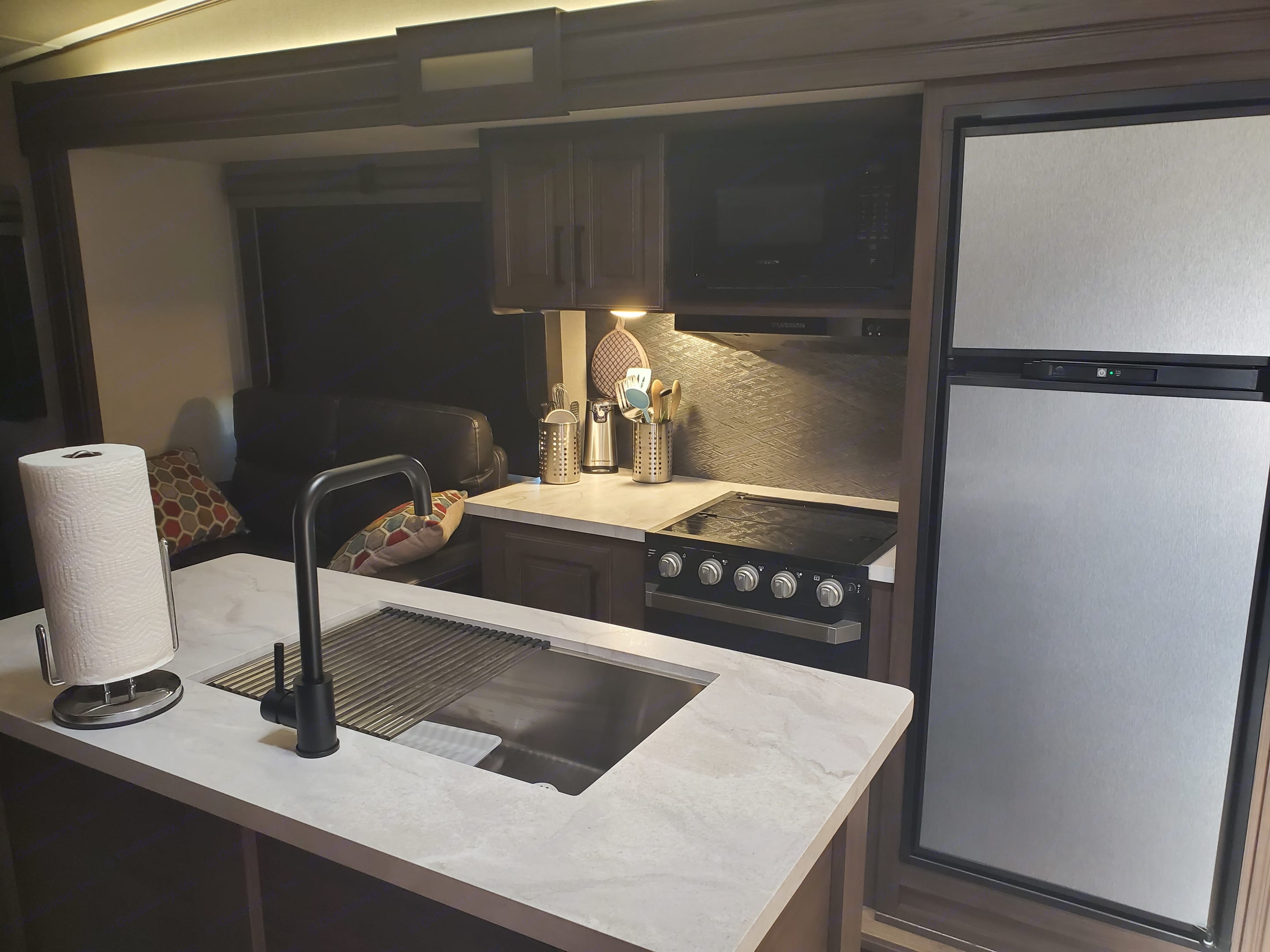 Island sink, 3 burner cook top and small oven, microwave and 8 cf refrigerator/freezer. Prime Time Crusader 2021