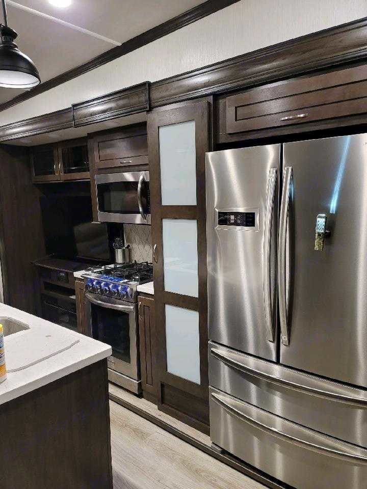 Residential size refrigerator with two freezer drawers and an ice maker.  . Forest River Cedar Creek Silverback 2021
