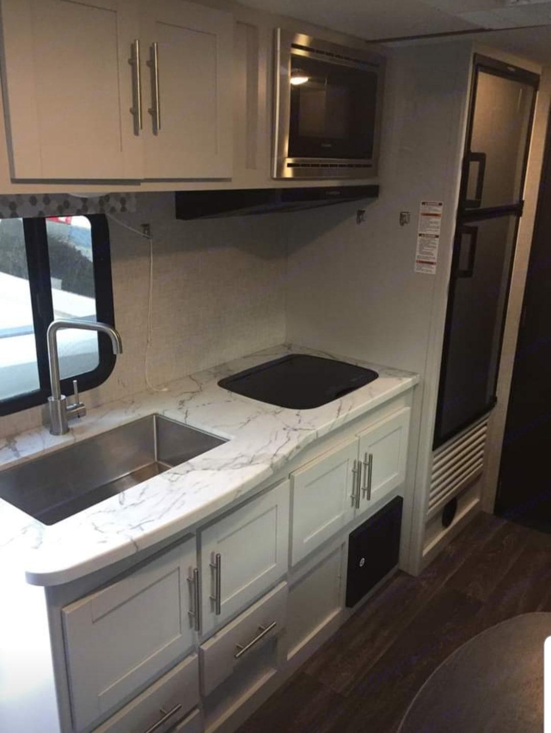 Deep stainless steel sink, real wood cupboards, 2 burner stove, microwave and generous fridge and freezer. . Keystone Bullet 2020