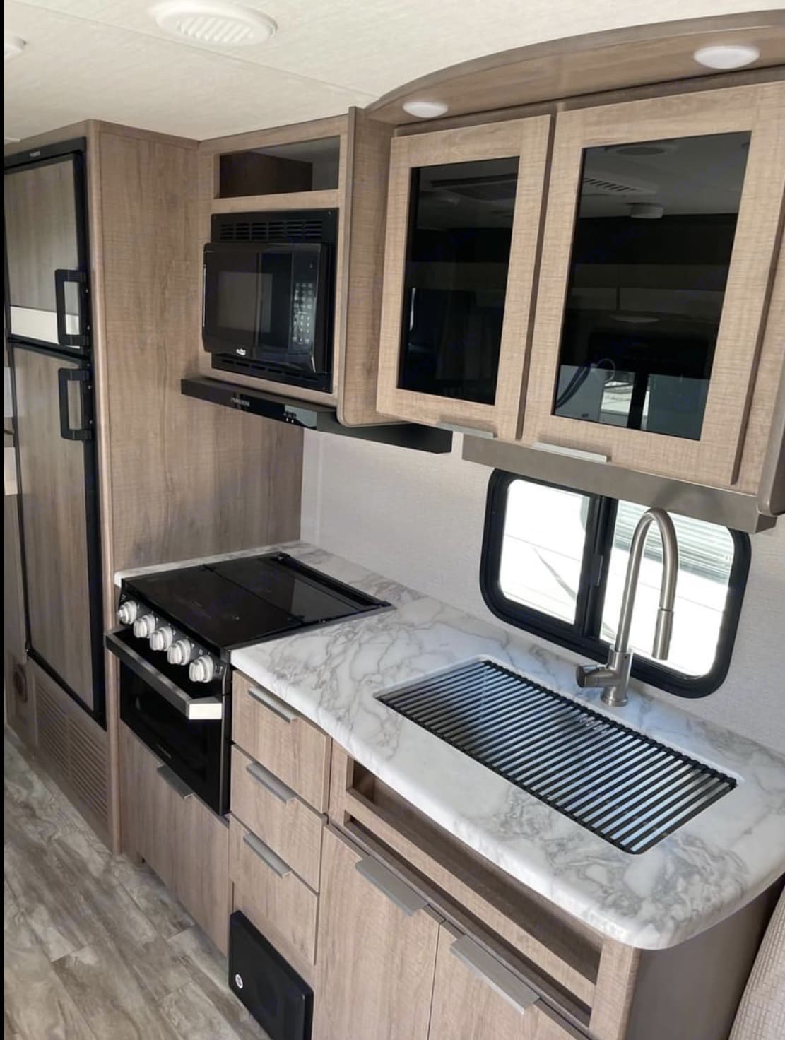 Kitchen with stove oven microwave refrigerator and freezer and audio controls above sink . Grand Design 21BHE 2021