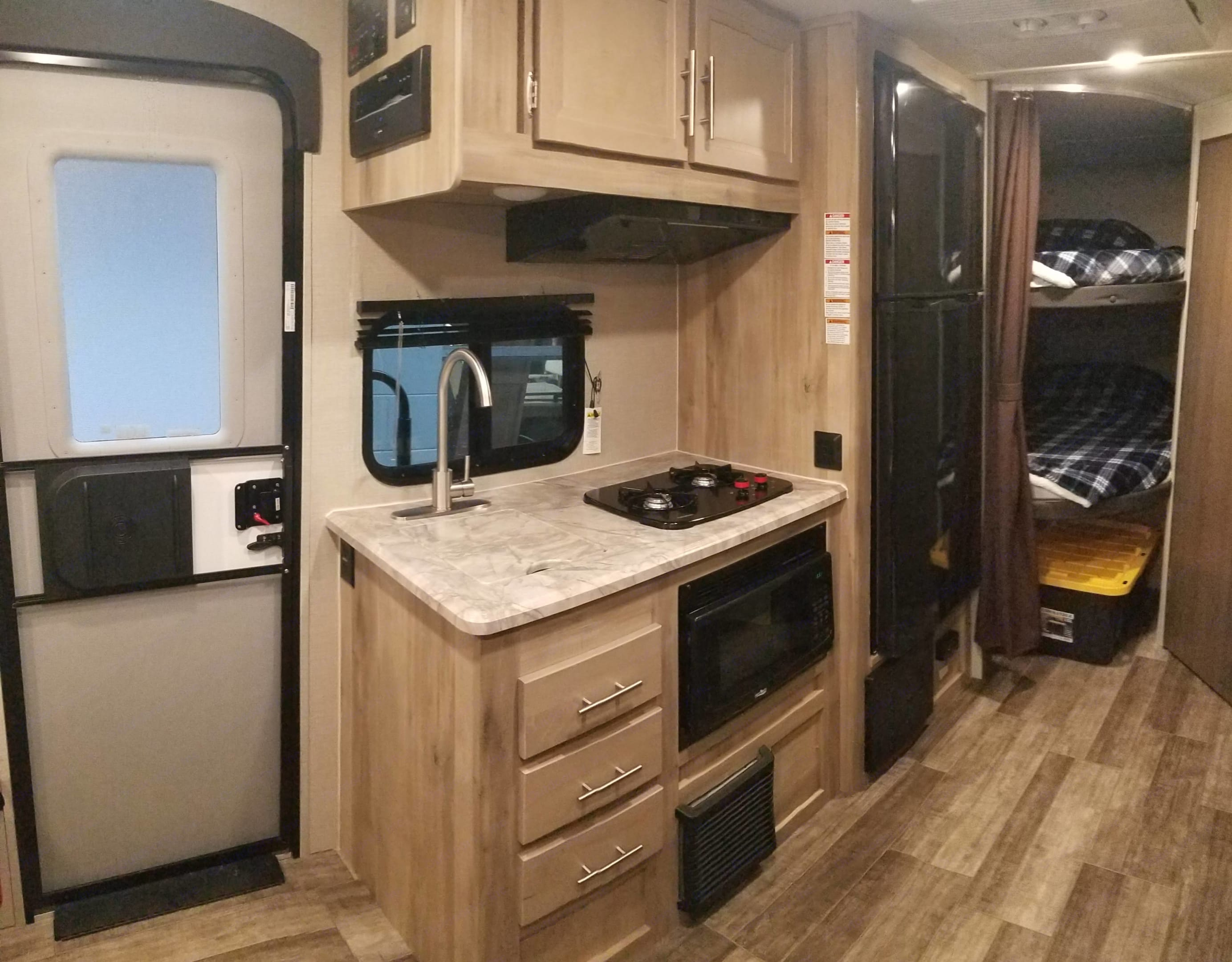 Kitchen with sink, microwave, 2 burner stove top and large fridge with freezer. Forest River Aurora 18BHS 2021