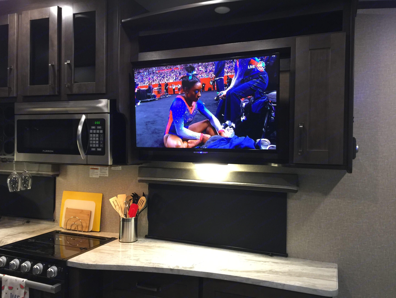 Microwave, stove, kitchen utensils, entertainment center. Grand Design Reflection 2021