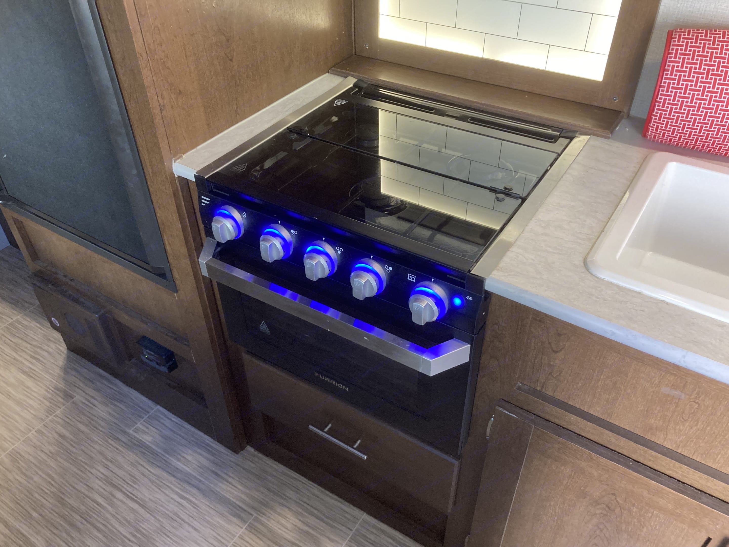 The propane stove has 4 burners and an oven. Above the stove is a microwave oven. . Prime Time Avenger 2019