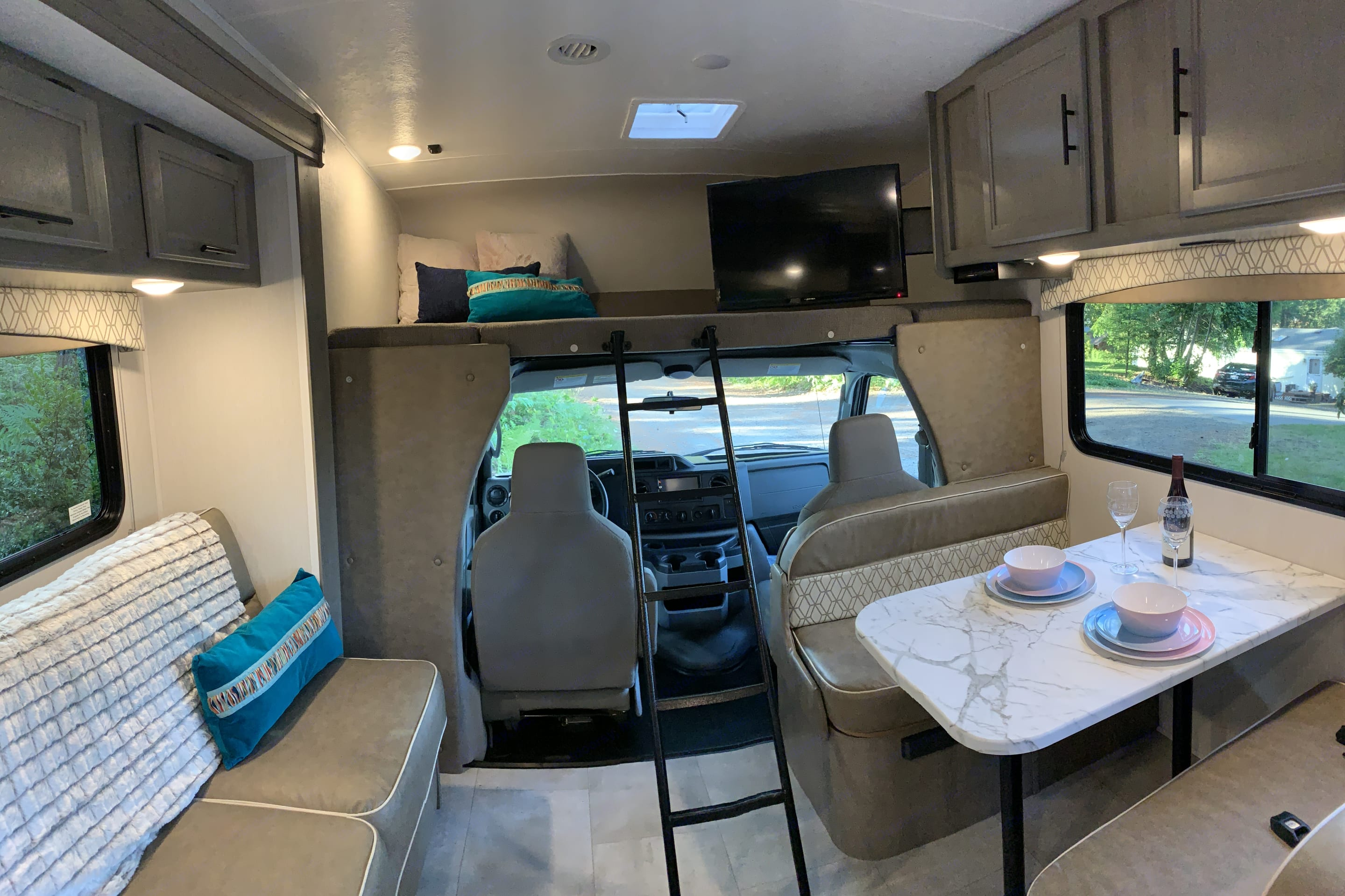 Our cab is nice and roomy for the driver and passenger. Over the cab is an additional large sleeping area and a TV. . Coachmen Freelander 2021