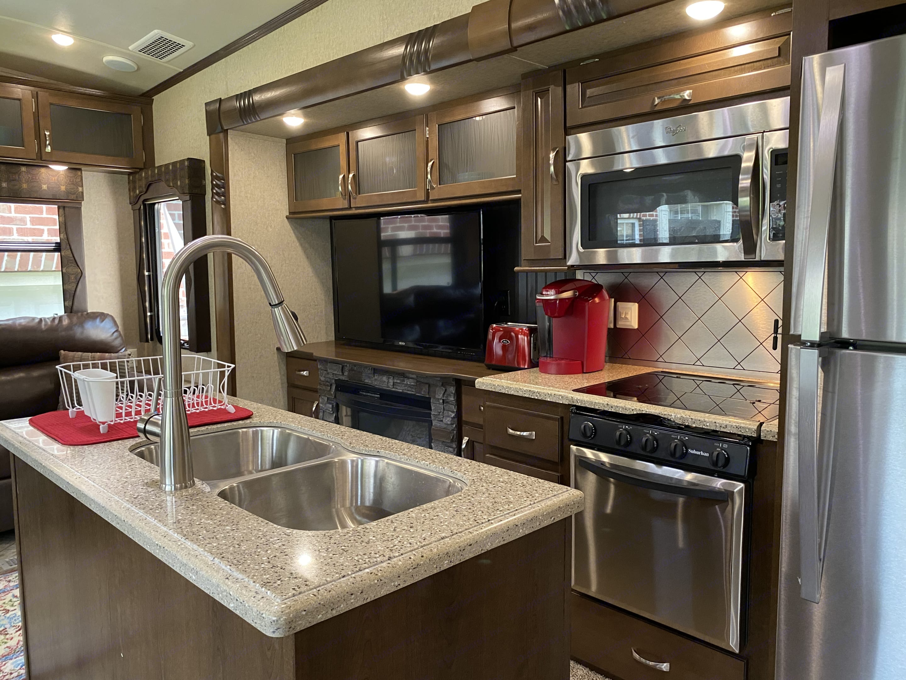 Full-size kitchen with 3 burner gas stove & oven, microwave, and large refrigerator/freezer. Coffee machine, toaster, table &  silverware for 4 incl.. Forest River Cedar Creek Fifth Wheel 2016