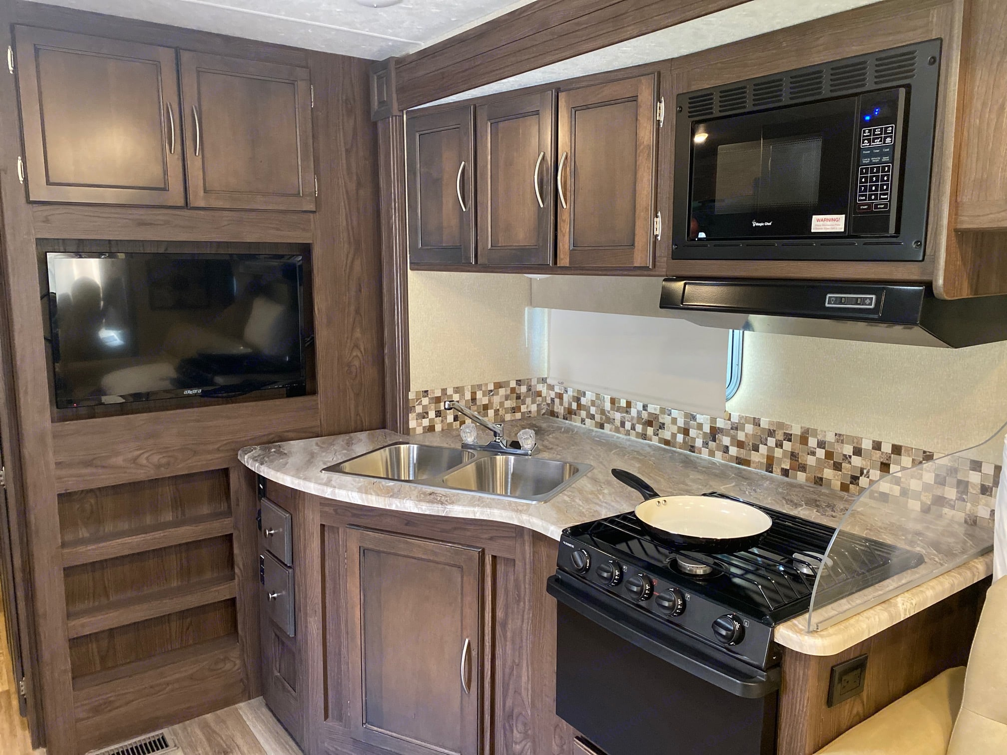 Kitchen area has a microwave, stove, oven, sink, TV, and refrigerator/freezer.  Plenty of cabinet and pantry space provided. . Coachmen Pursuit 2019