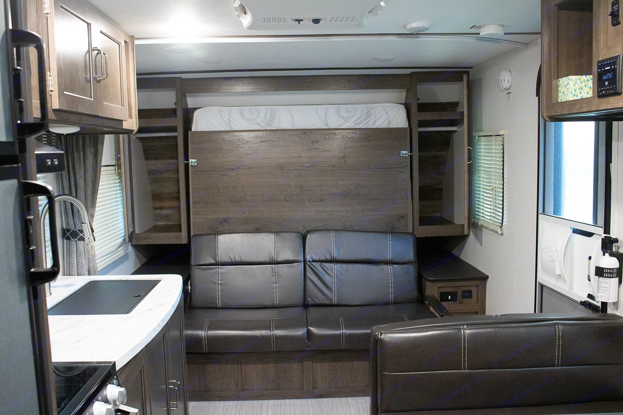 Bed folds up and turns into a good sized leather couch. USB power outlets on both sides. Deep cabinets with hanging bar for clothes or other storage. . Keystone Passport 2019