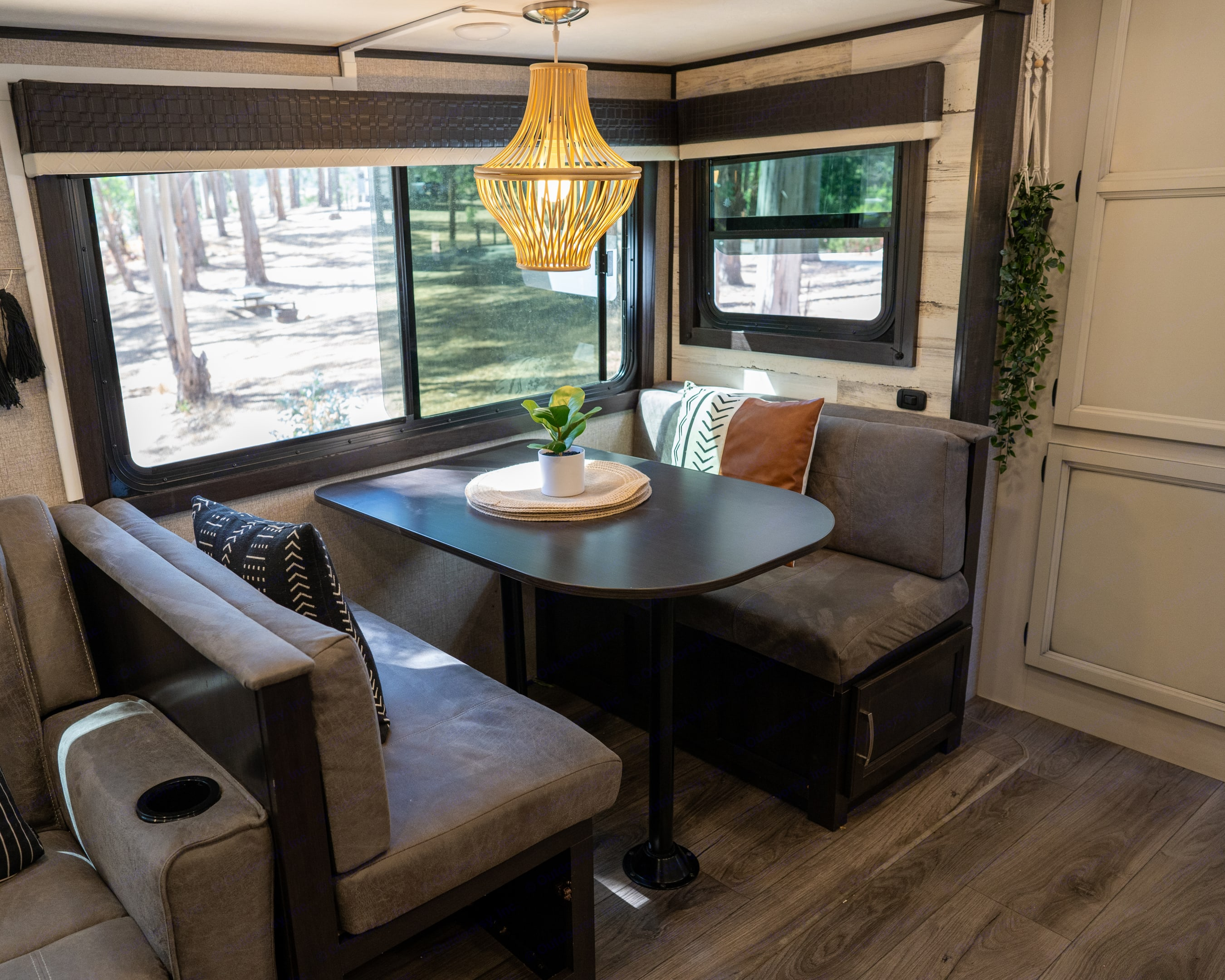 Four seater dinette with bohemian light fixture and five shelf pantry. Dinette also converts into a double bed.. Jayco Jay Feather 2021