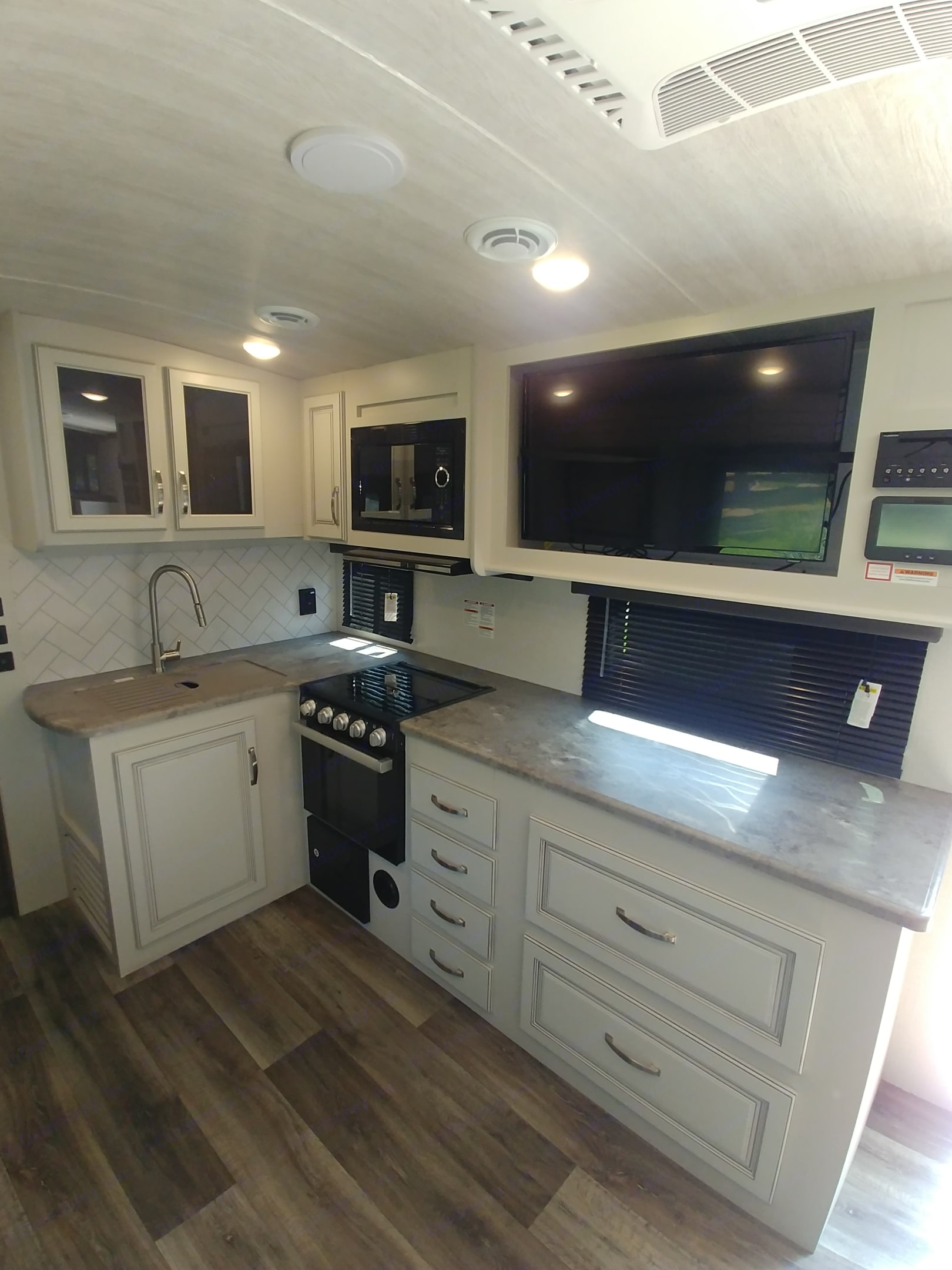 Kitchen with TV/DVD player, microwave, 3 burner stove, oven and sink with plenty of storage.. Keystone Cougar Half-Ton 2021