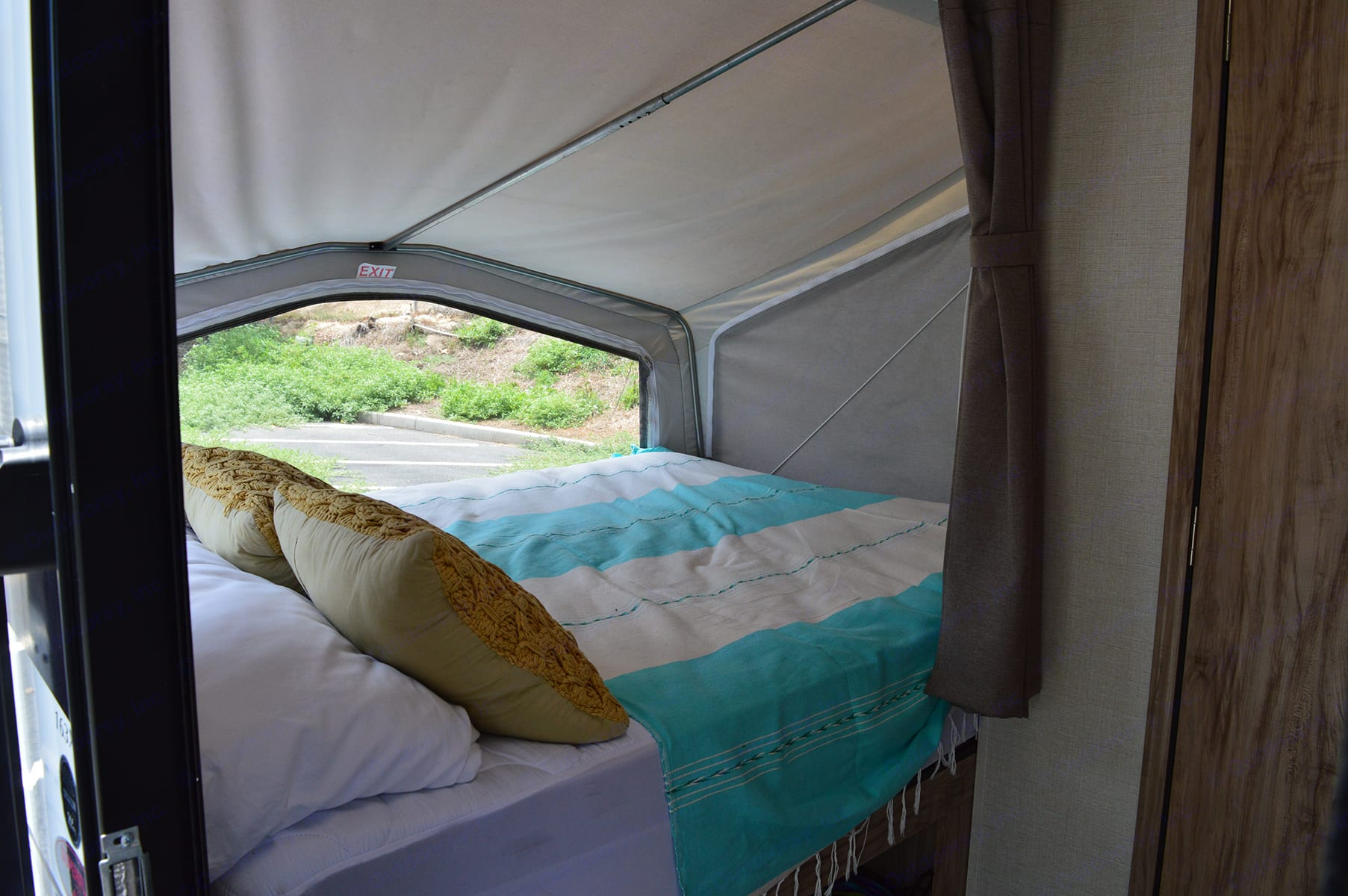 Queen bed at rear of RV. Palomino Solaire Expandable 2020