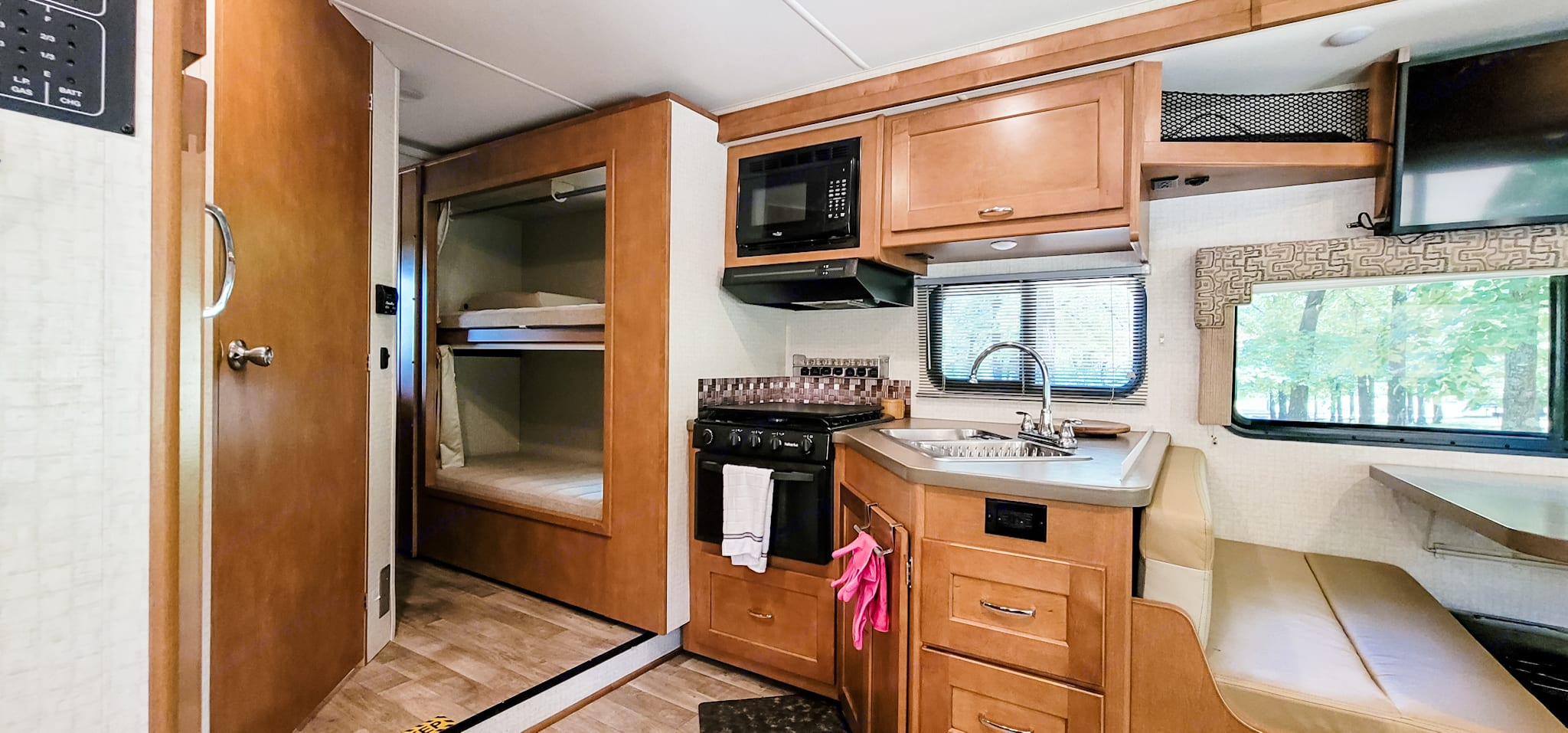 This kitchen has a two compartment sink, 3 burner stove, oven, and microwave.  Comes loaded with cookware, utensils, plates glasses and silverware.. Winnebago Minnie Winnie 2018