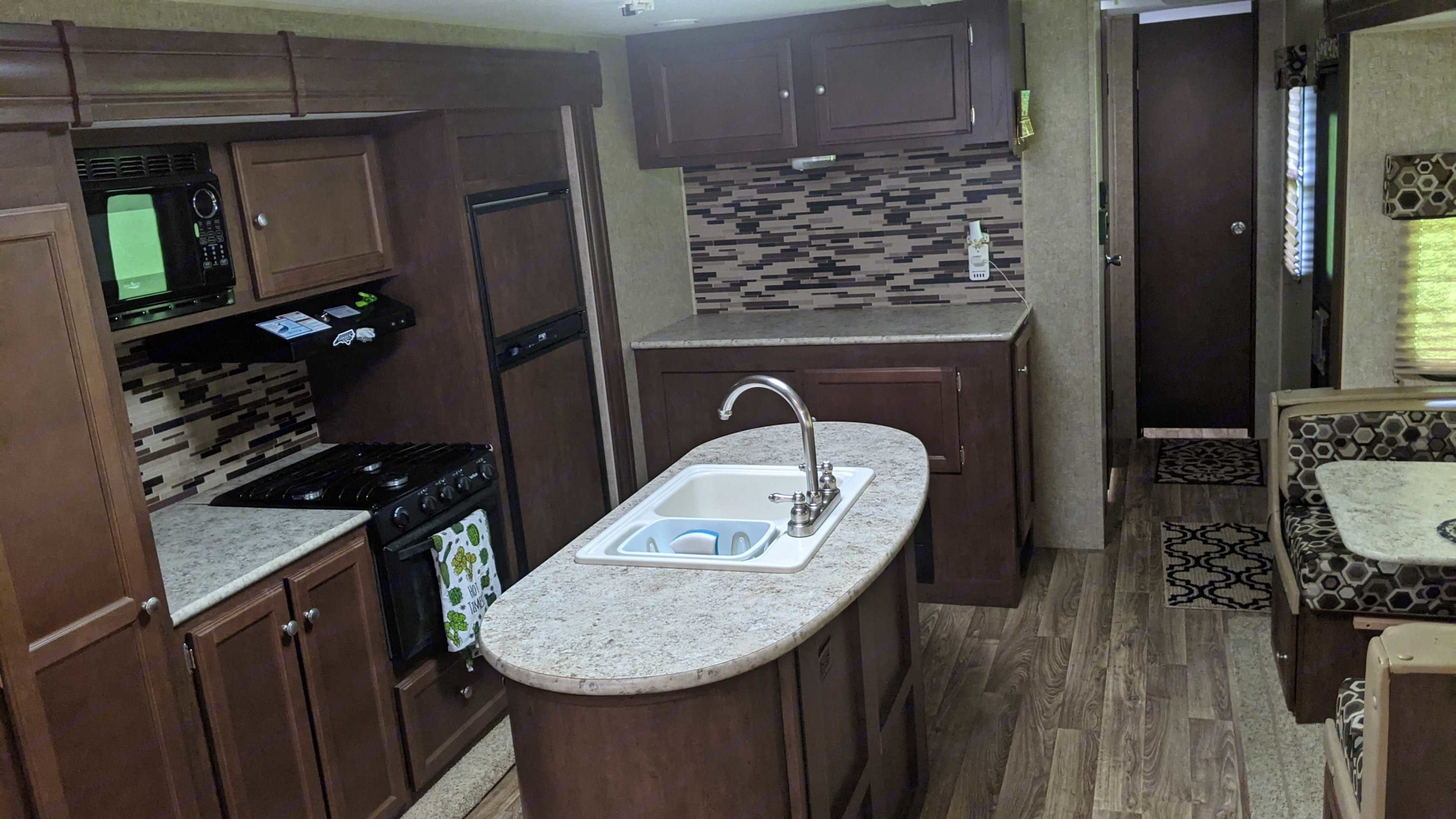 A kitchen with an island and eat in dining area!. Venture Rv Sporttrek 2015