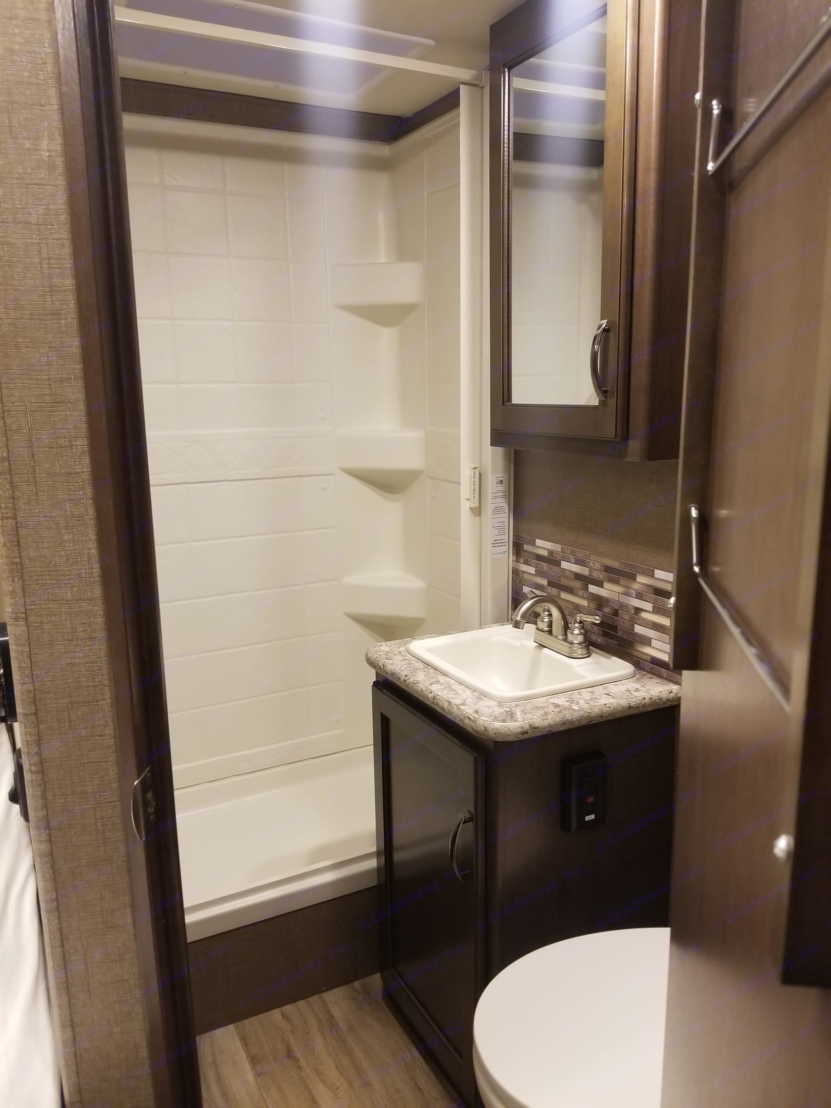 Standing shower includes slide out shower door. The flushable RV toilet is just in front of the sink on the right side.. Thor Motor Coach Freedom Elite 2017