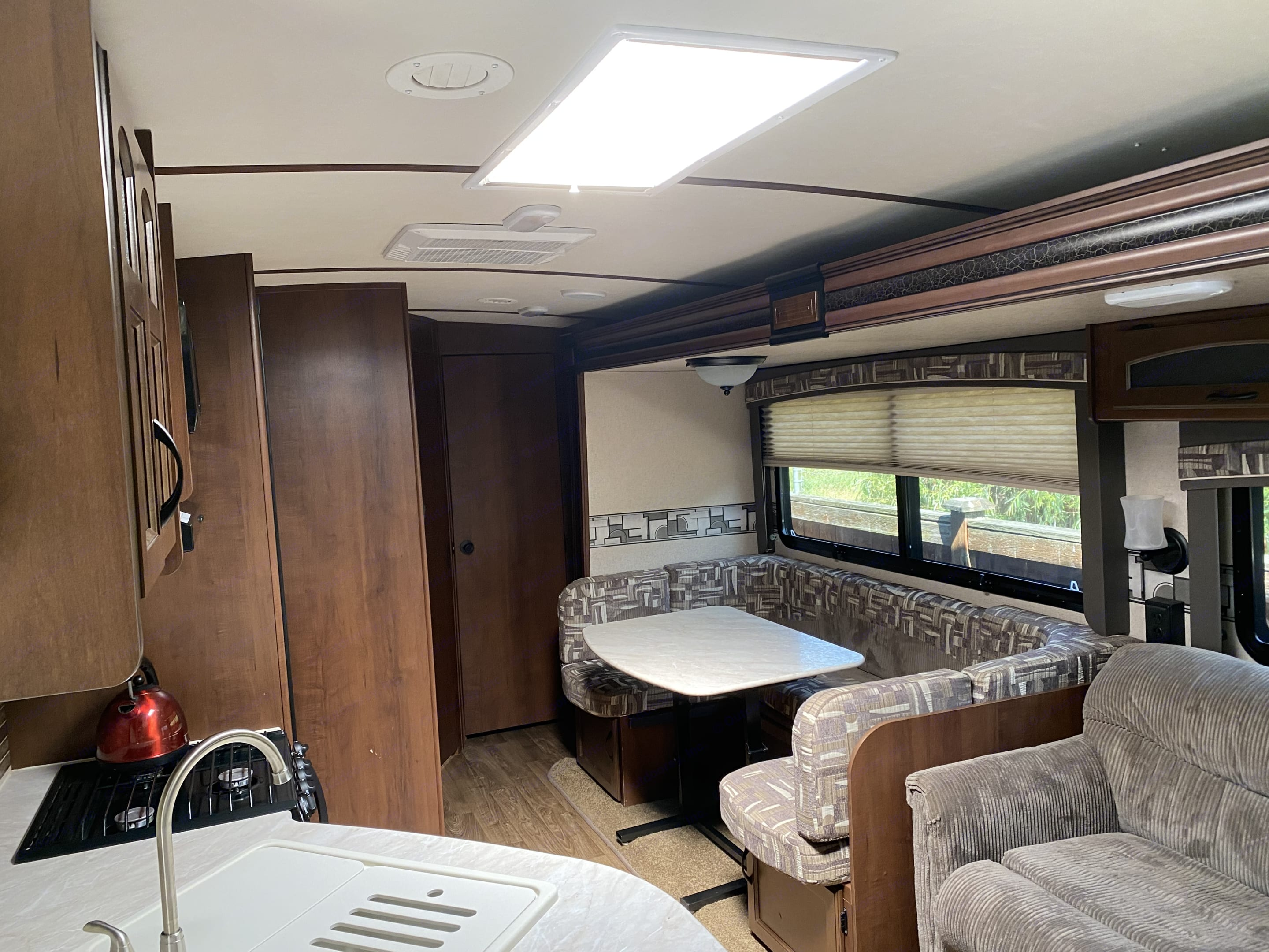 This area shows the interior with kitchen table and couch.  Not pictured is tv/dvd system.  Slides are not all the way out.. Jayco White Hawk Ultra Lite 2015