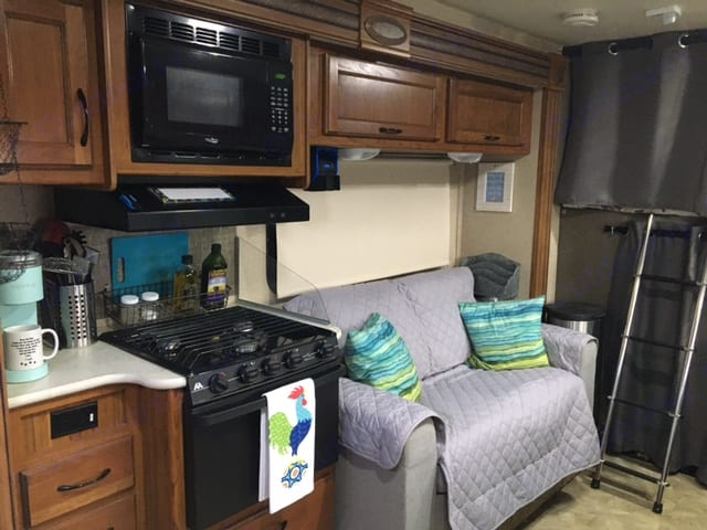Storage under and over sofa with overhead fan and opening screened windows with shade for privacy. Jayco Redhawk 2016