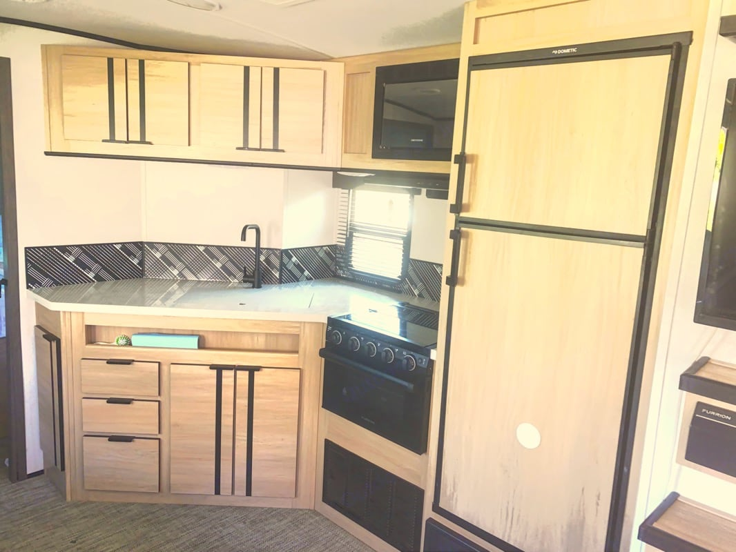 Kitchen has gas stove, oven, and microwave.. Cruiser Rv Corp Radiance 2021