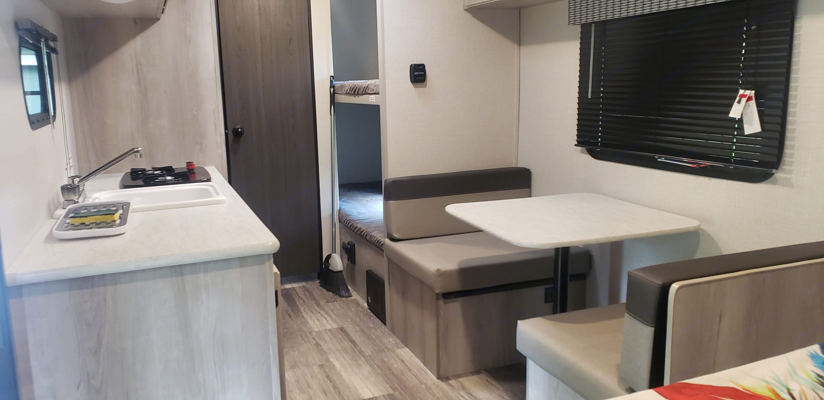 Serve meals at the small but functional dinette from the kitchen featuring sink, two-burner stove, microwave, fridge/freezer combo, & lots of storage.. K-Z Manufacturing Sportsman Classic 2021