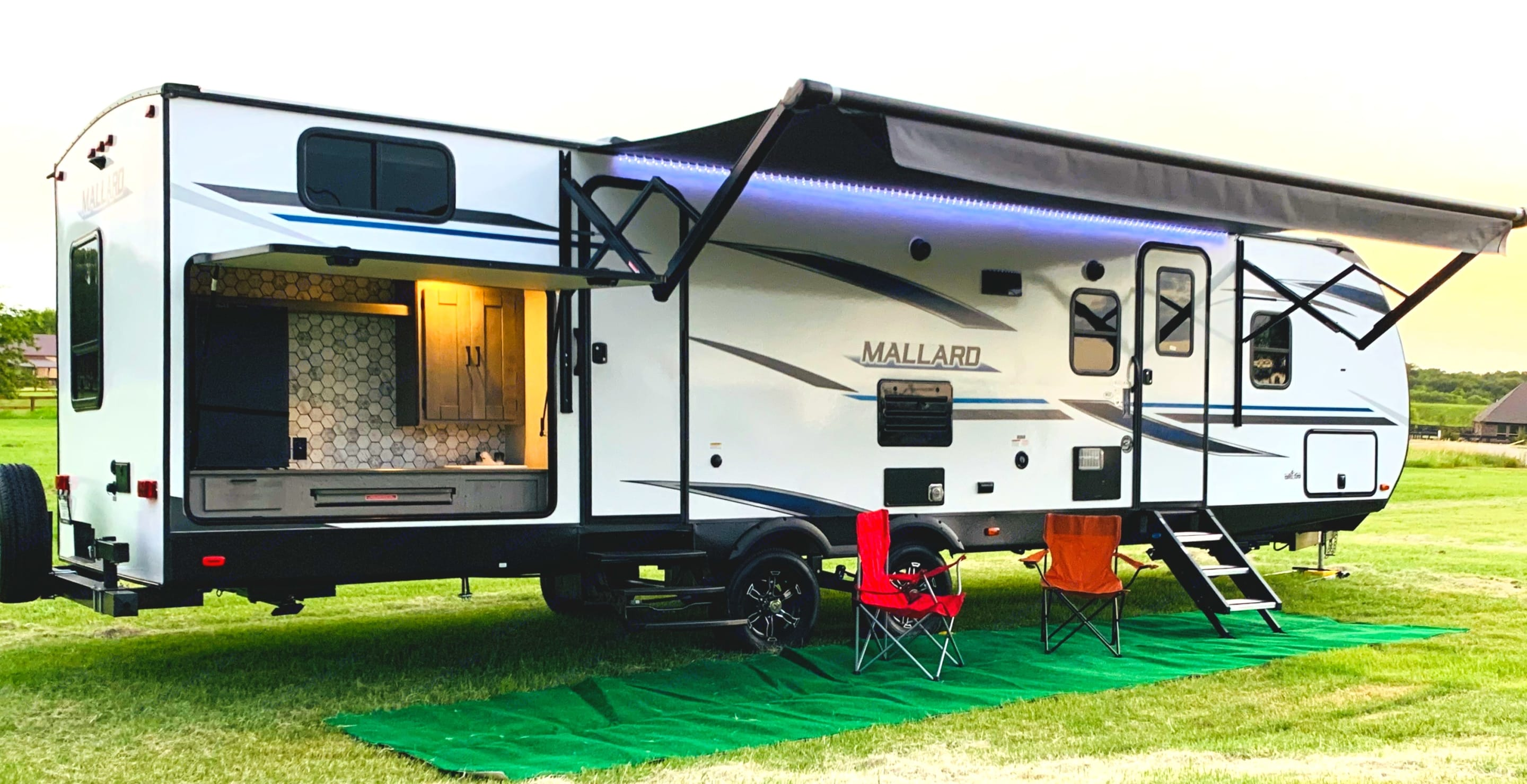 Exterior view with outdoor kitchen (Propane grill included) along with fridge and storage. Heartland Mallard M33 2021