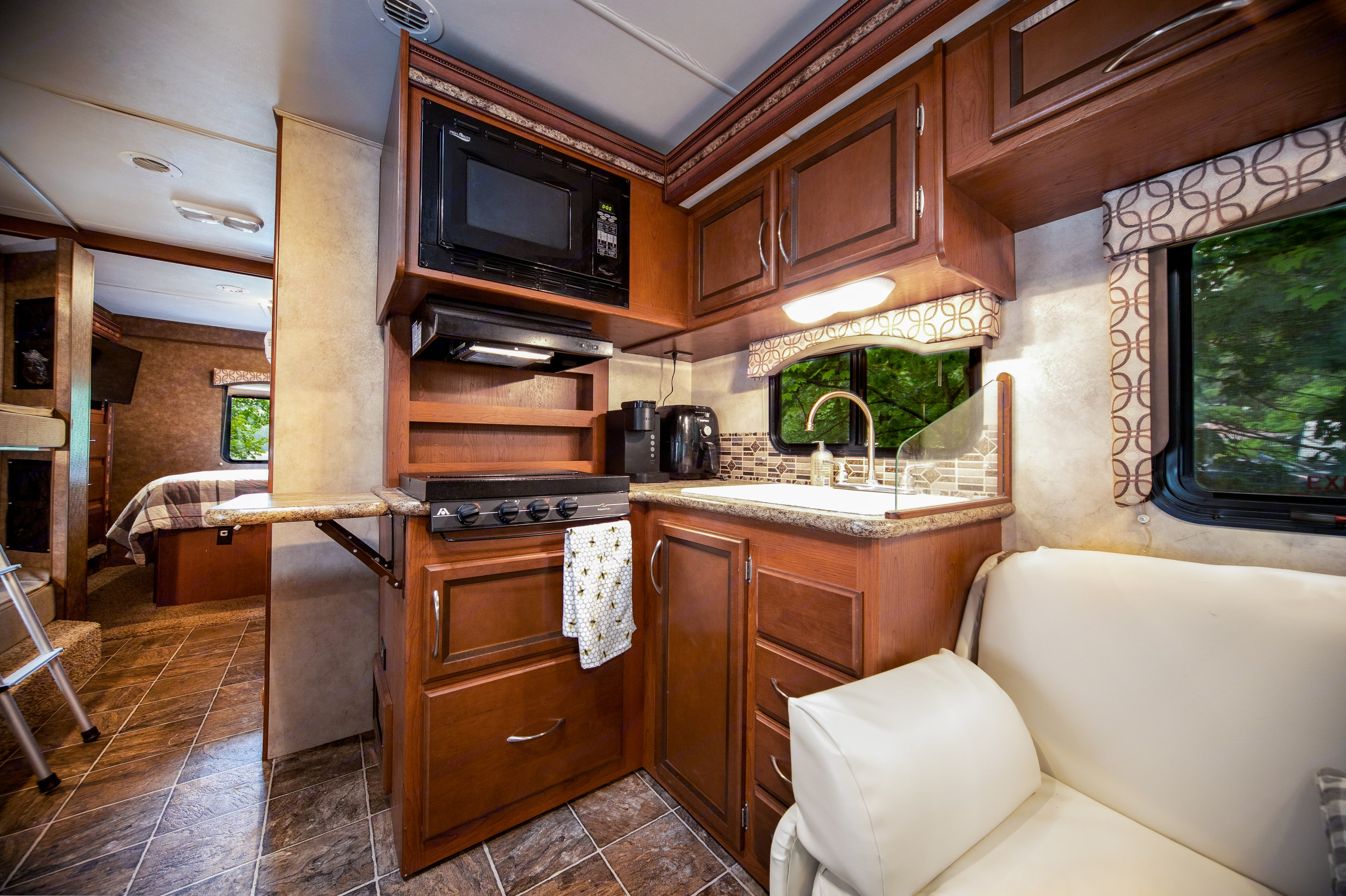 Kitchen area includes a sink, microwave, propane stove top, Keurig and air fryer.. Thor Motor Coach Four Winds 2013