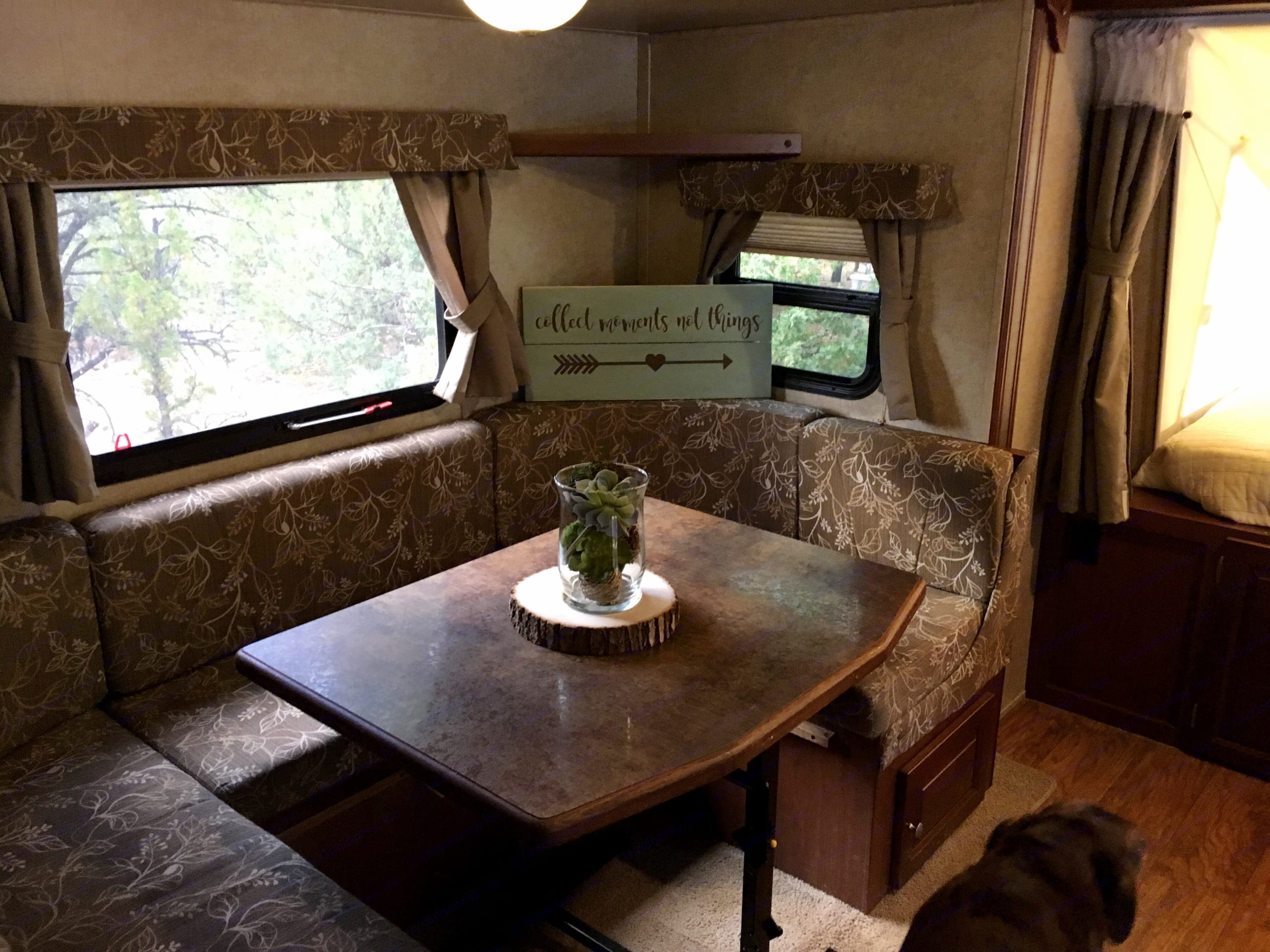 U-shaped dining table that also converts to a queen size sleeping area.  Storage under both side bench seats.  Windows on three sides provide plenty of light and breeze.. Forest River Rockwood Roo 2015