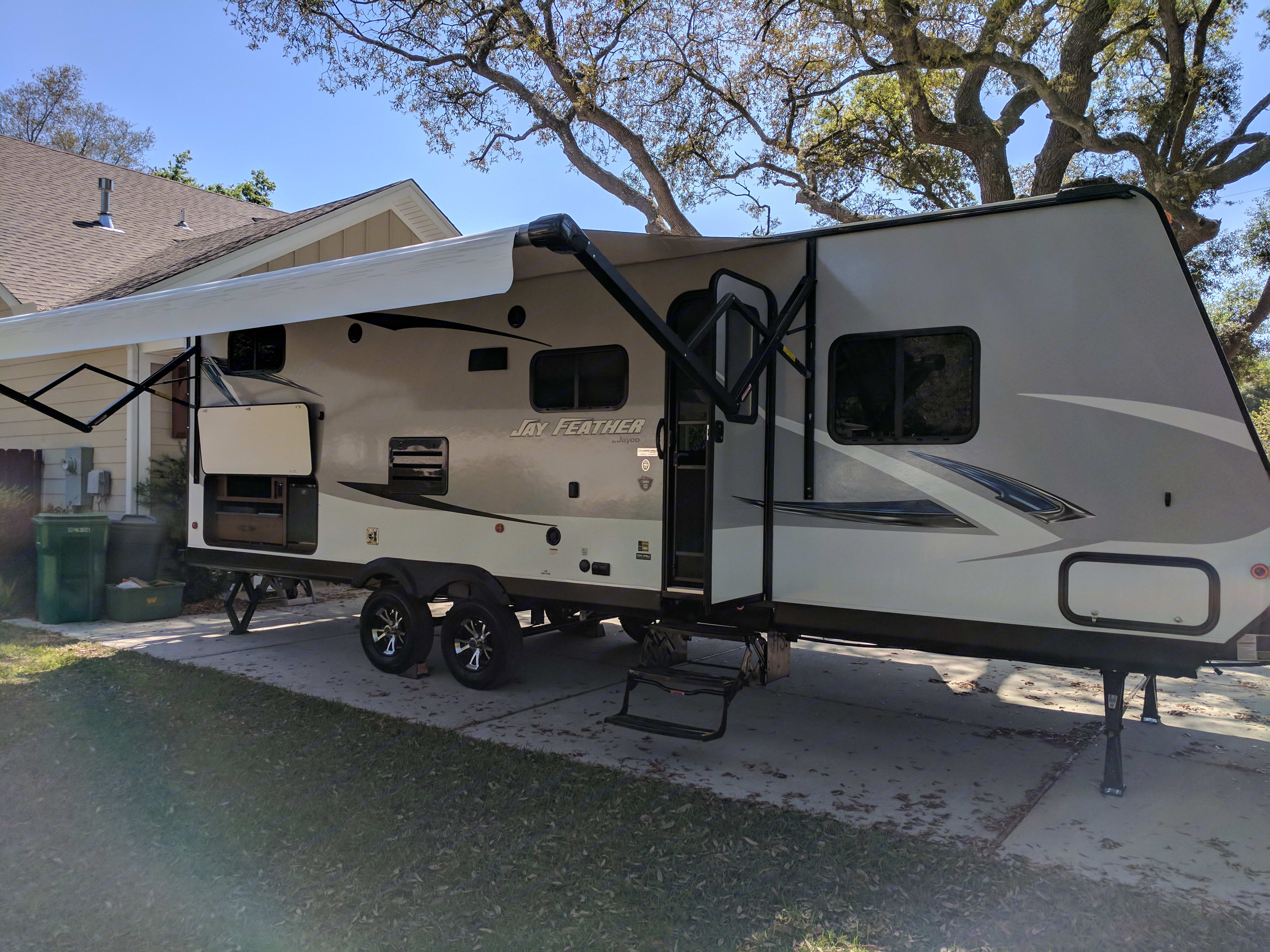 Outdoor two burner stove top with sink and refrigerator located under the awning. . Jayco Jay Feather 2017