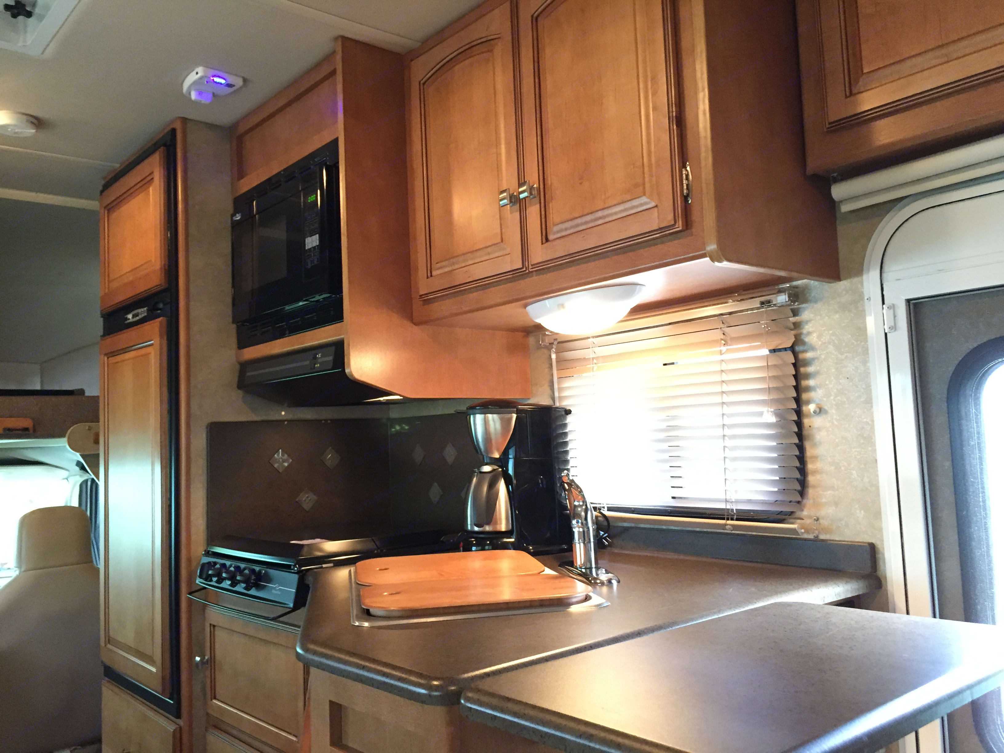 Kitchen with a large fridge and freezer, microwave oven, 3 burner stove, double sink and lots of storage. . Winnebago Access 2013