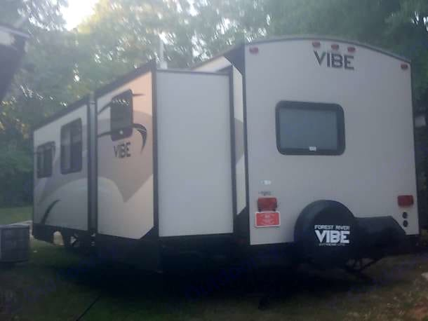 View from rear of RV, showing slides out and the gas grill with cover folded back against bumper. slides are in bunkroom and living/dining area. Forest River Vibe 312BHS 2016