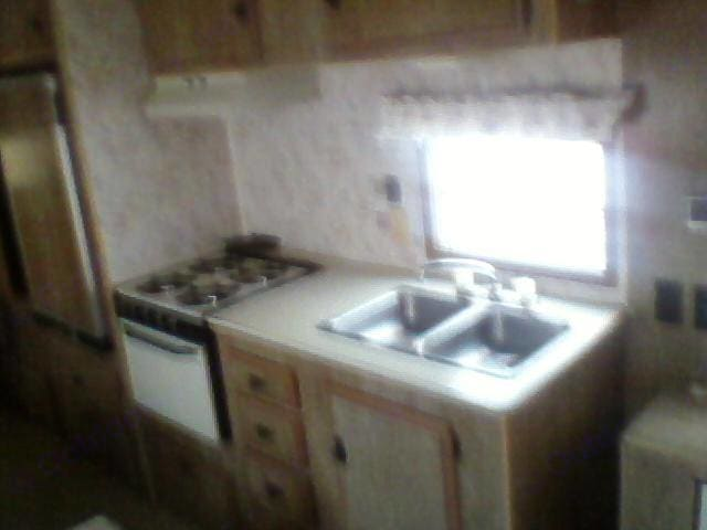 Full kitchen with stove, oven, sink and fridge.. Heartland Prowler 1983