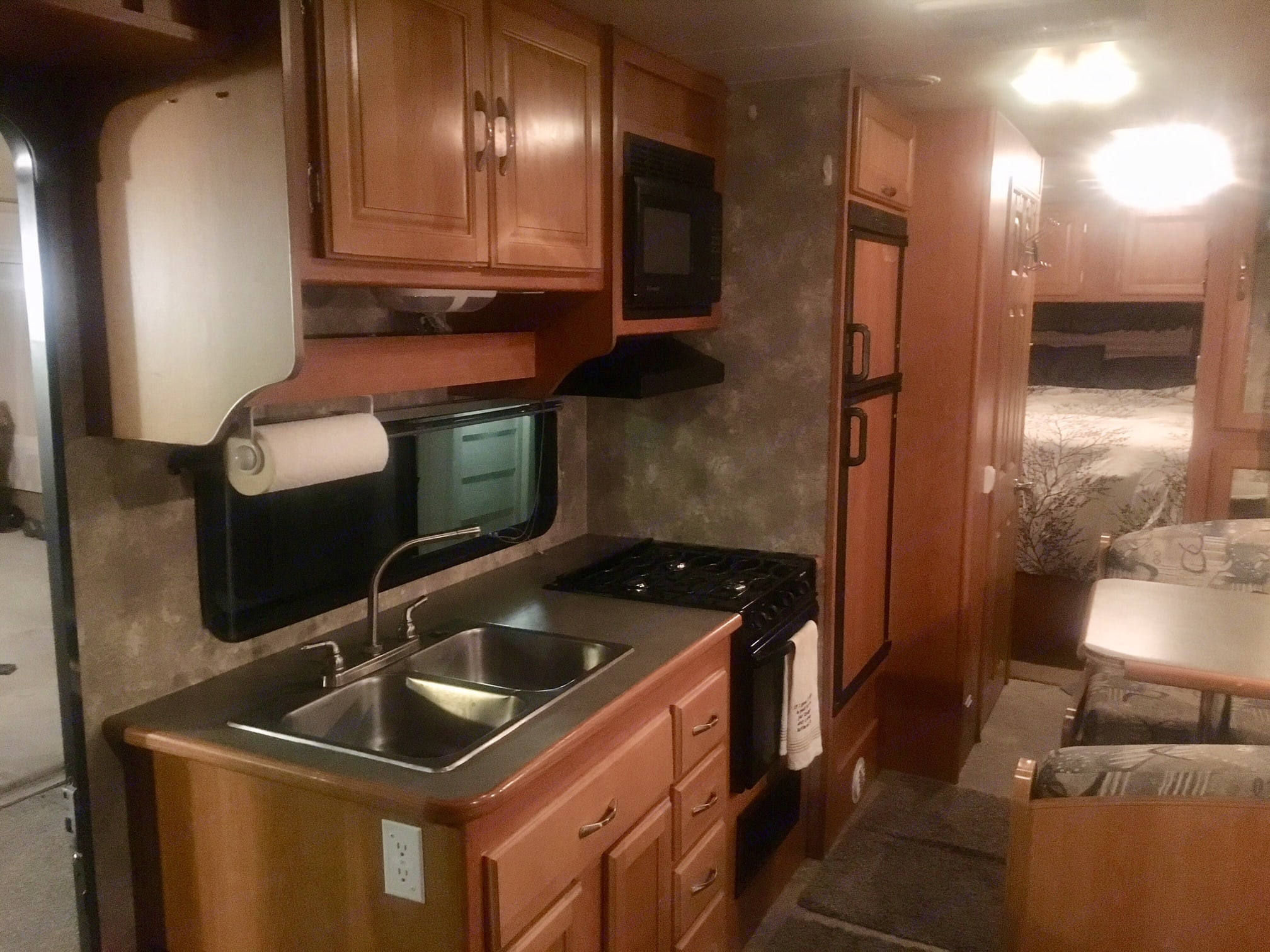 Large functional kitchen with refrigerator/freezer, 3 burner stove top, propane oven and double sink. Fully stocked with plates, silverware, cooking utensils, pots and pans, glasses, coffee cups, single use Keurig, and more.. Coachmen Freelander 2007