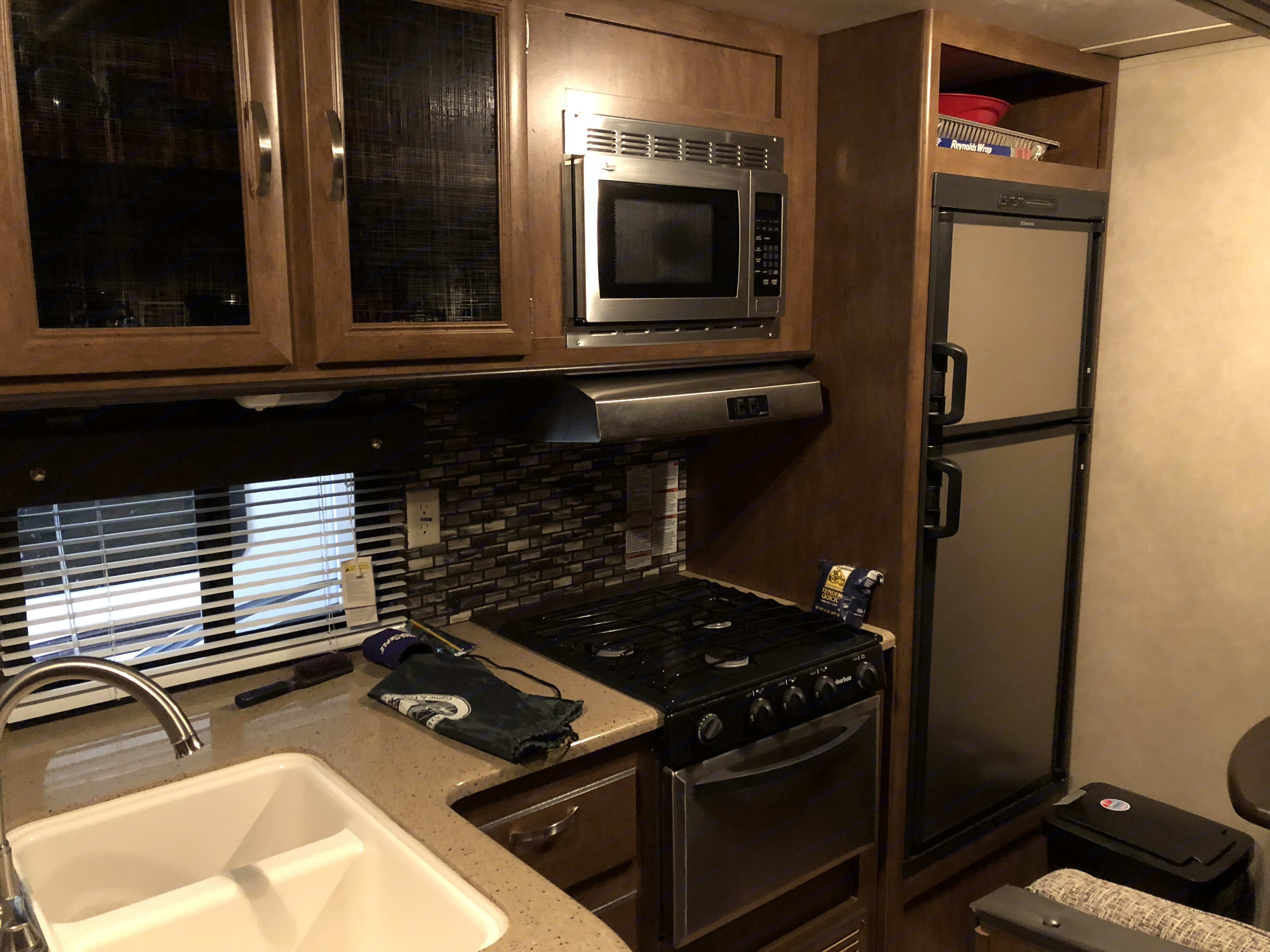 Kitchen with microwave, stove with oven & refrigerator freezer. . Wildwood 32qbss T31KQBTS 2015