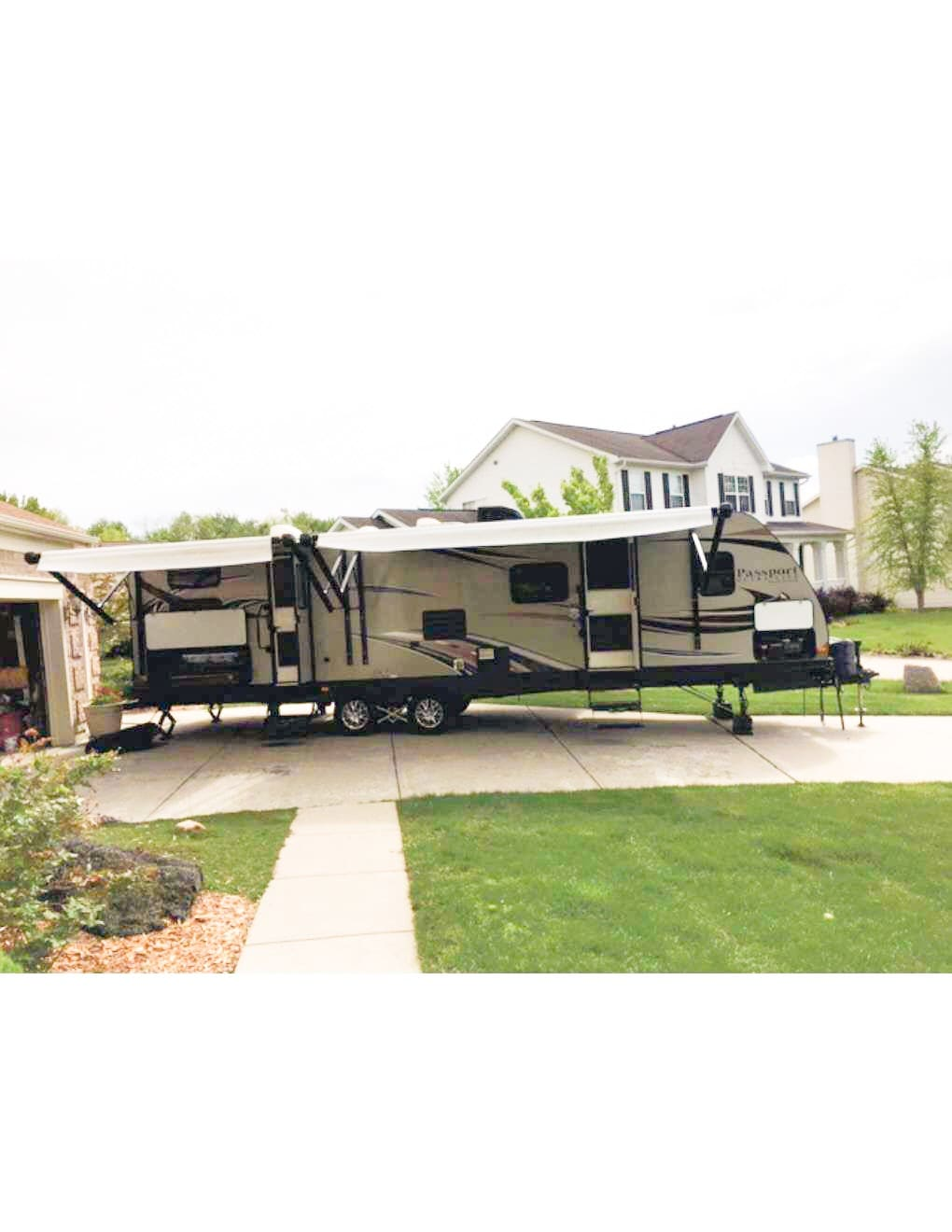 An outdoor view of the trailer. Take note of the large awnings, two entry doors and outdoor kitchen. . Keystone Passport 2014