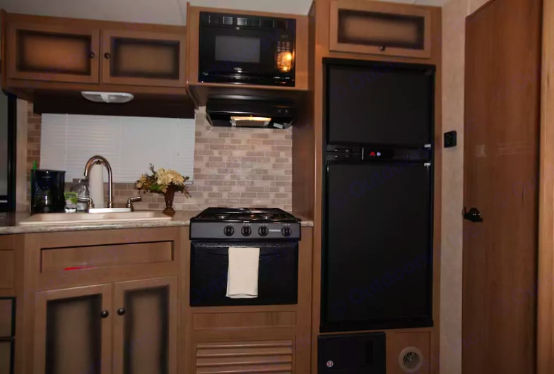 Full kitchen with fine finishes, double-sided porcelain sink, gas grill, microwave, coffeemaker, freezer and refrigerator.. Cruiser Rv Corp Radiance 2015