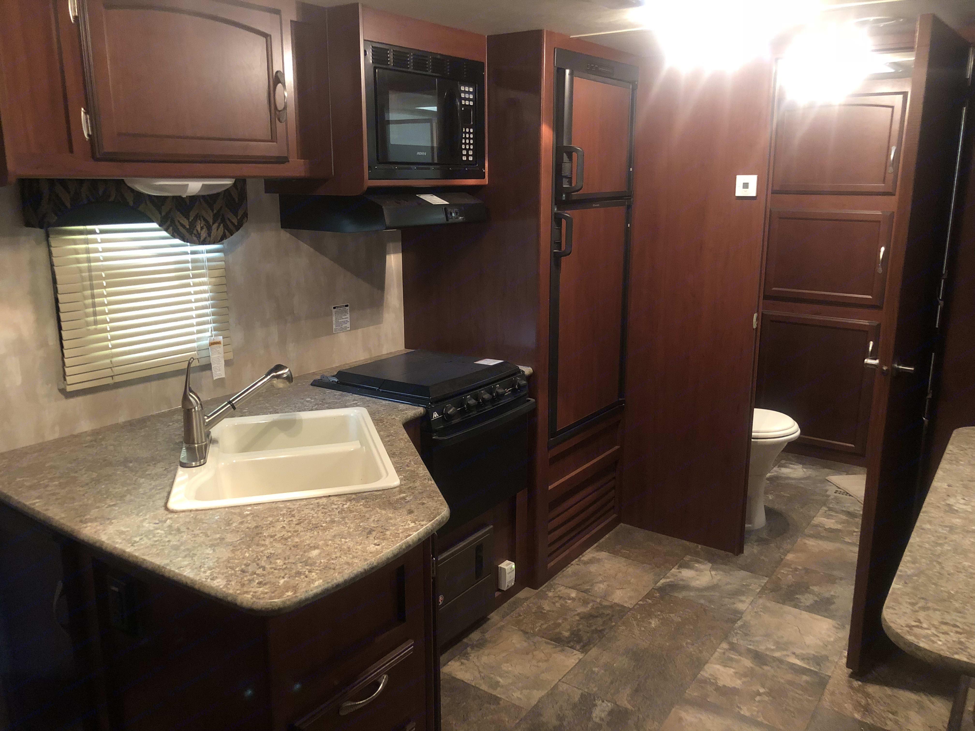 Kitchen includes sinks, oven, 3 burner stove, microwave, fridge and freezer. . Winnebago Minnie Winnie 2015