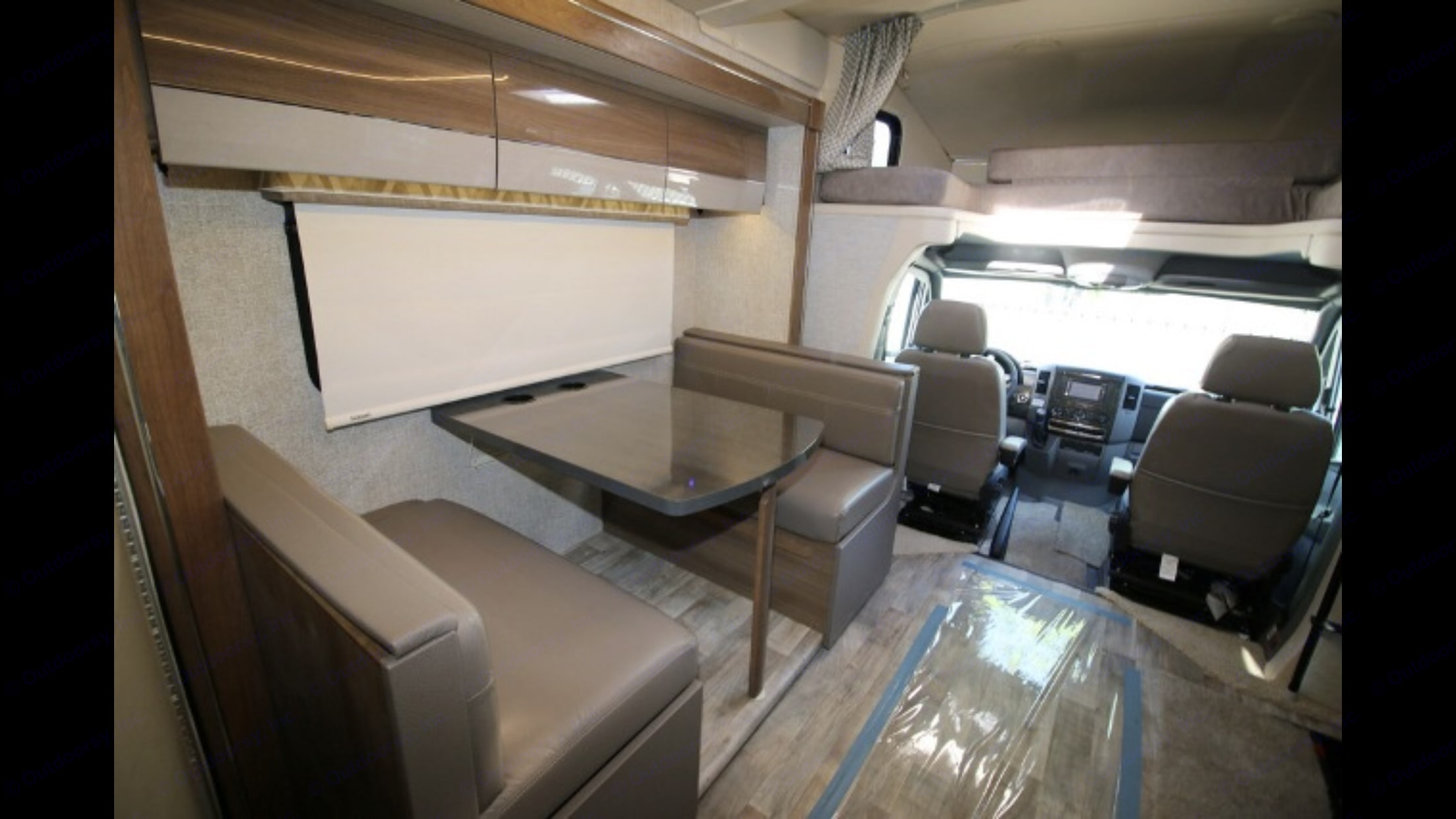 Interior slide extended out view of dinette table with comfortable Leather seating . Winnebago Navion 24G 2017