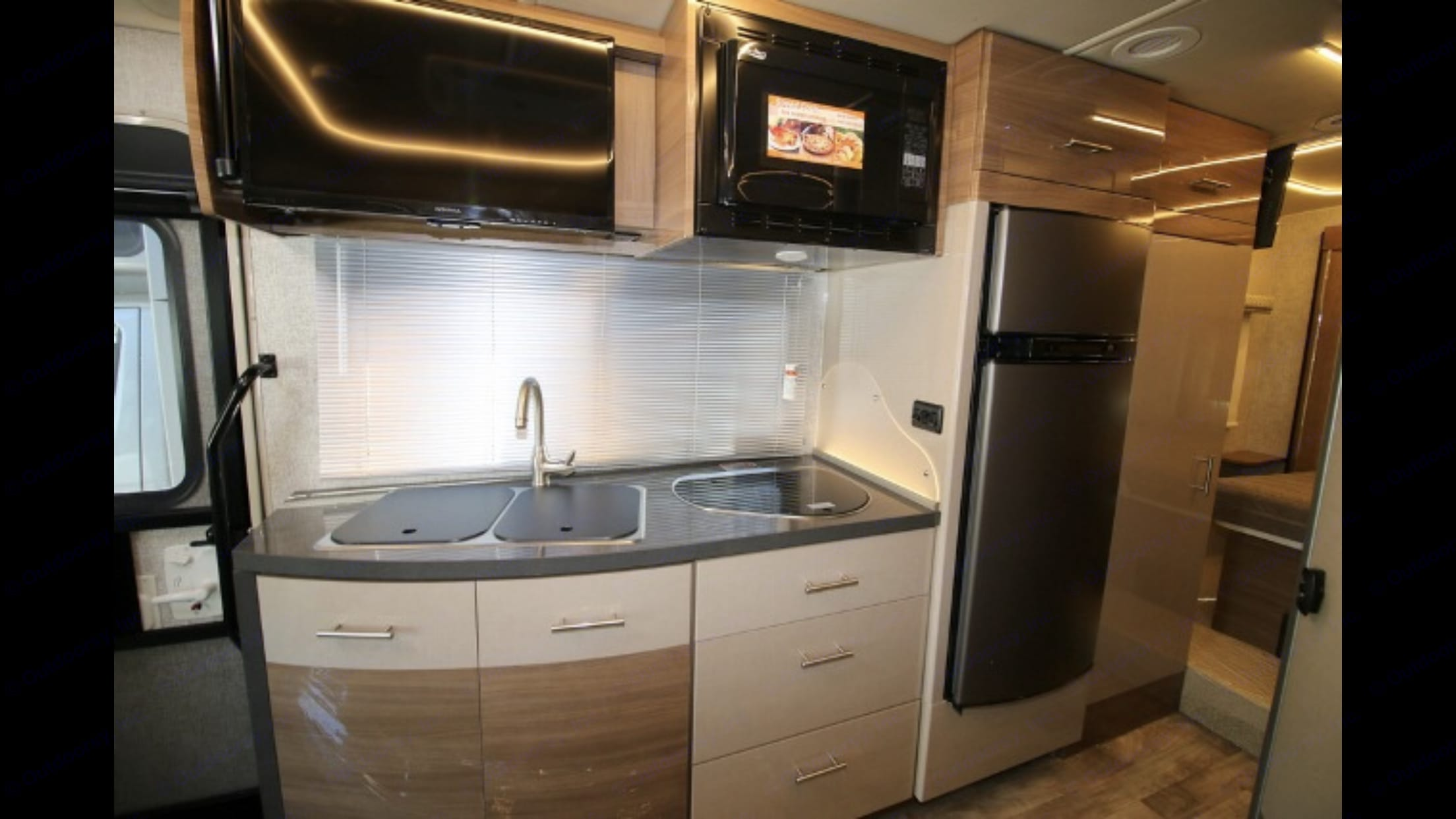 View of Kitchen sink and 2 burner propane stove TV and microwave -convection oven and Refrigerator Frezzer wardrobe closet view. Winnebago Navion 24G 2017