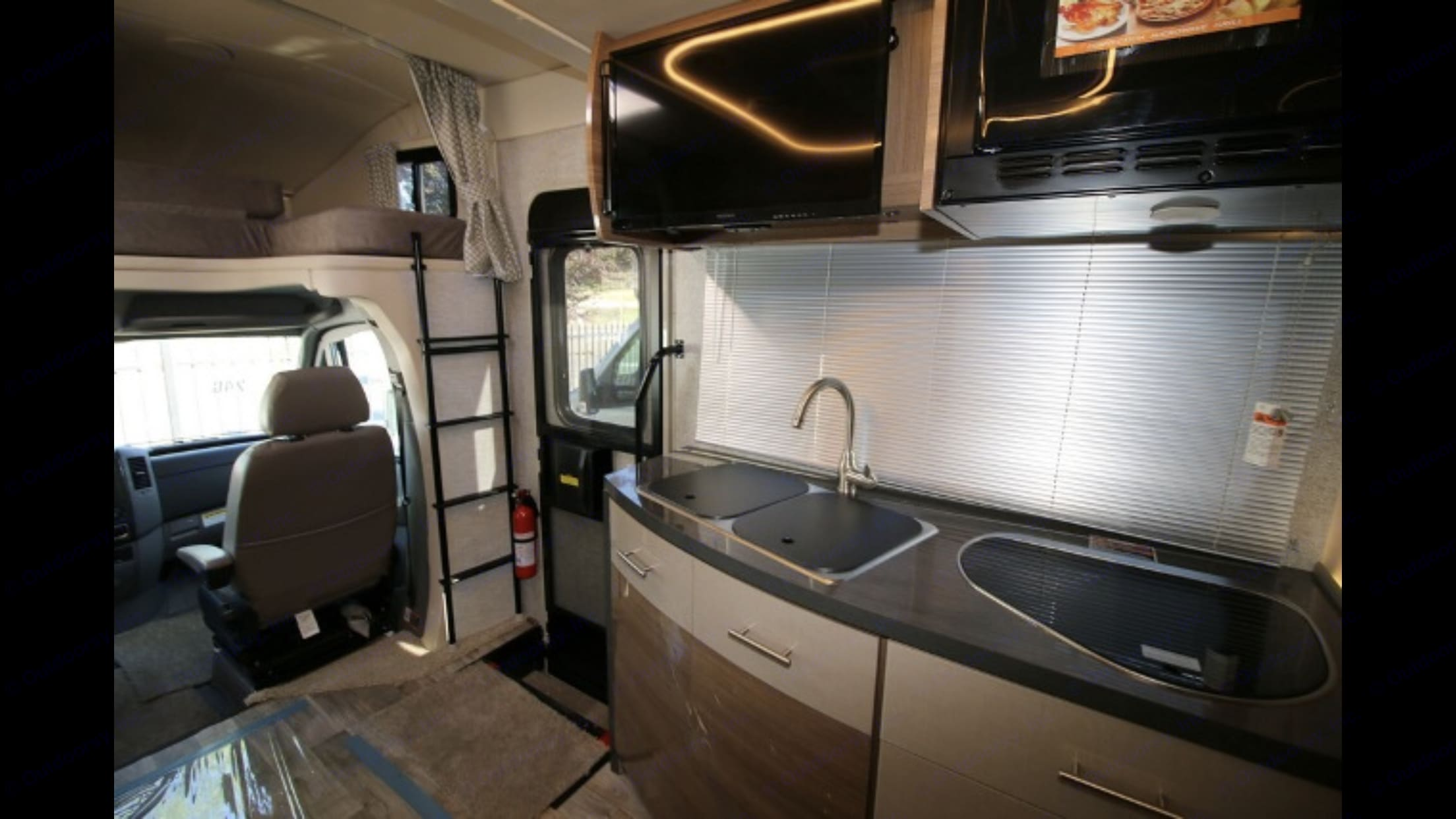 View of Kitchen and locked in place ladder for bunk bed over cab - Fire Extinguisher . Winnebago Navion 24G 2017