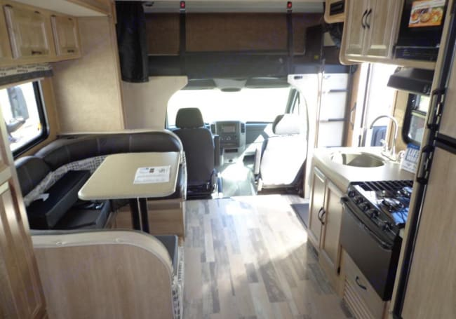 Dinette has 5 seat buckles and folds into a bed, over cab bed. Driver and passenger seats turn around for extra seating.  Sink stove refrigerator. . Coachmen Prism 2015