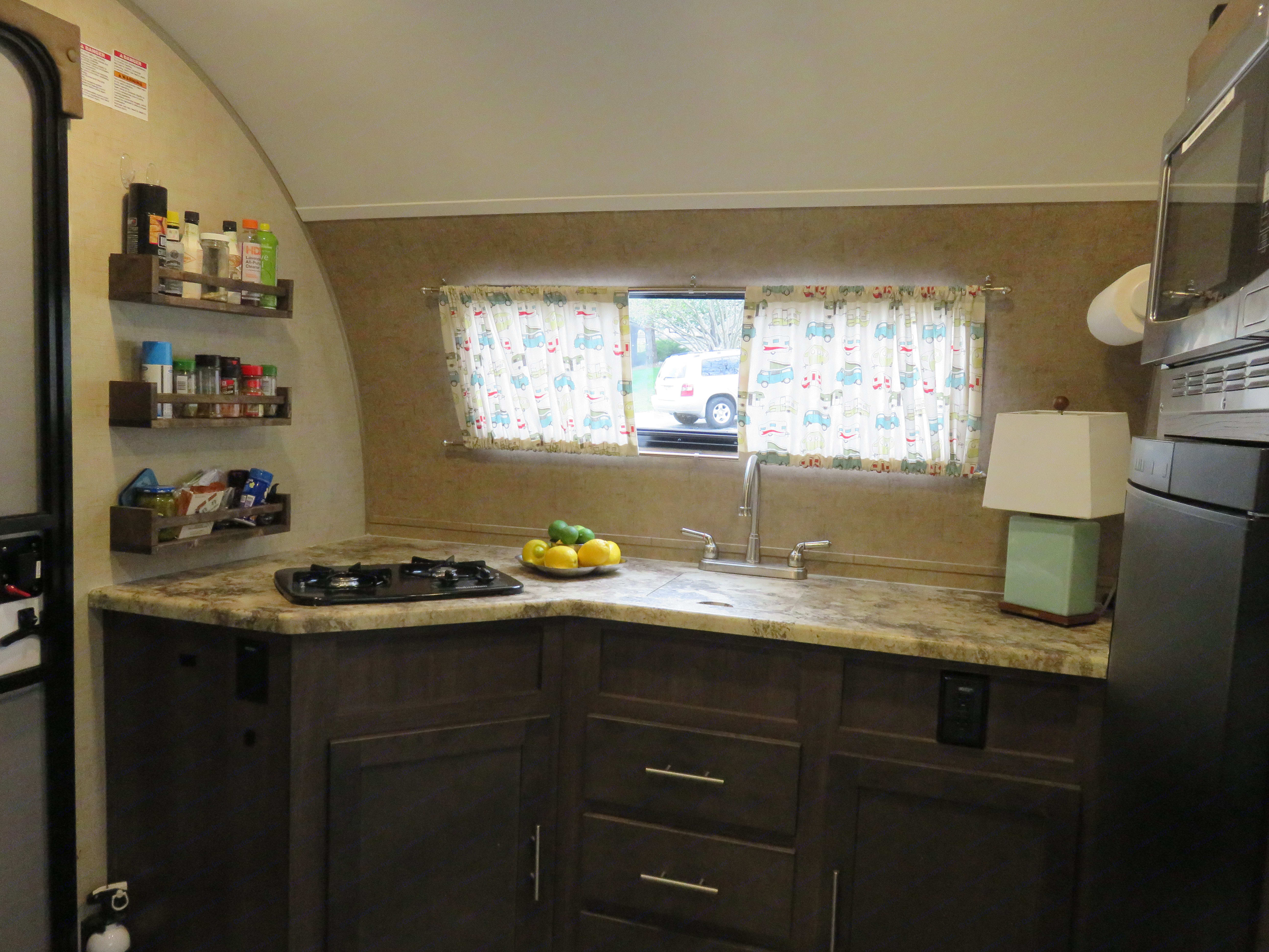 """The kitchen has plenty of light and is conveniently located at the door of the """"pod"""". The kitchen has a 2 burner gas stove, sink, refrigerator - freezer, microwave convection oven and plenty of storage. Oh, don't forget the pantry.. Forest River R-Pod 179 2016"""