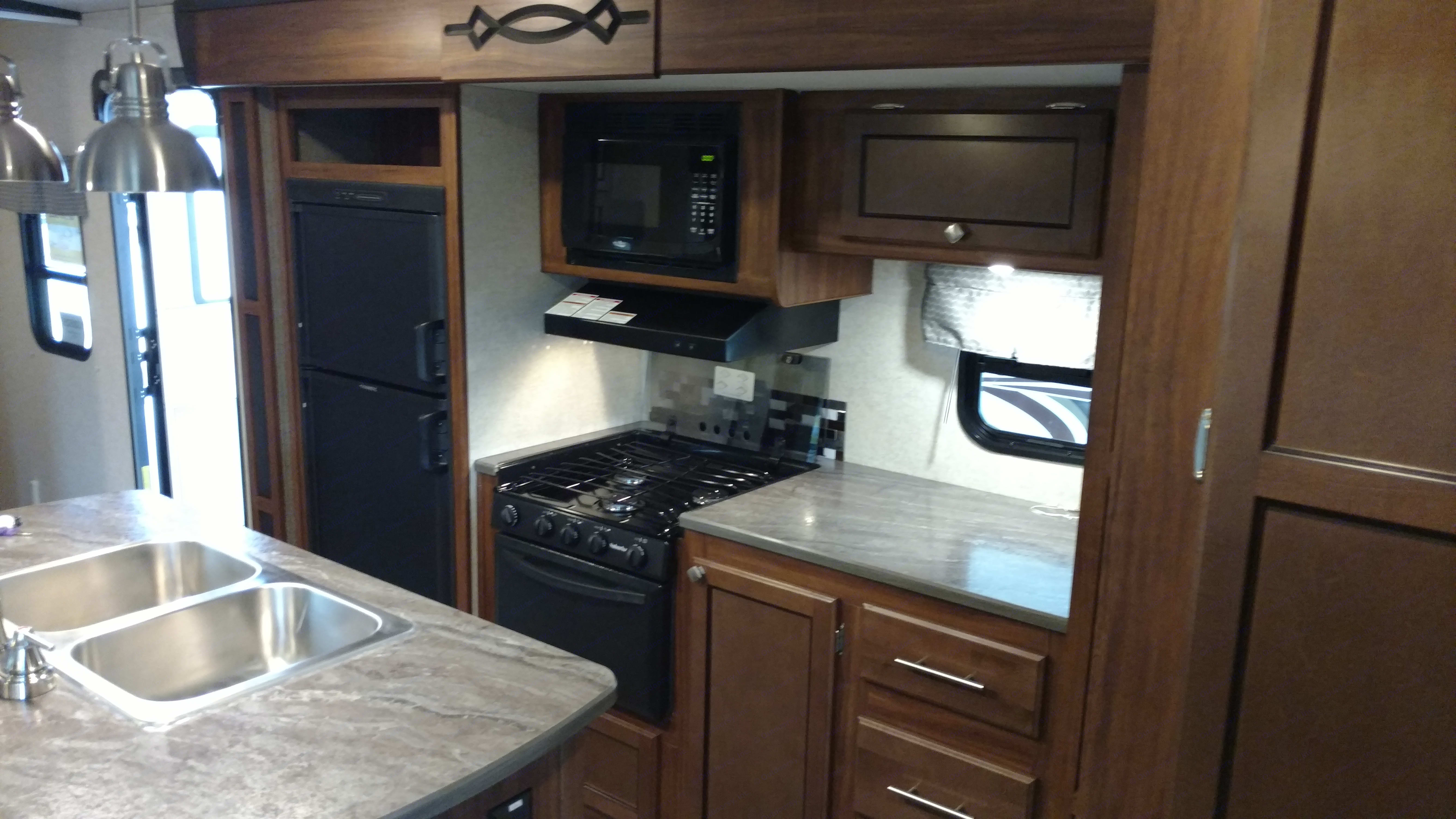 Kitchen, showing island sink, stove/oven, and refrigerator.. Heartland Other 2017