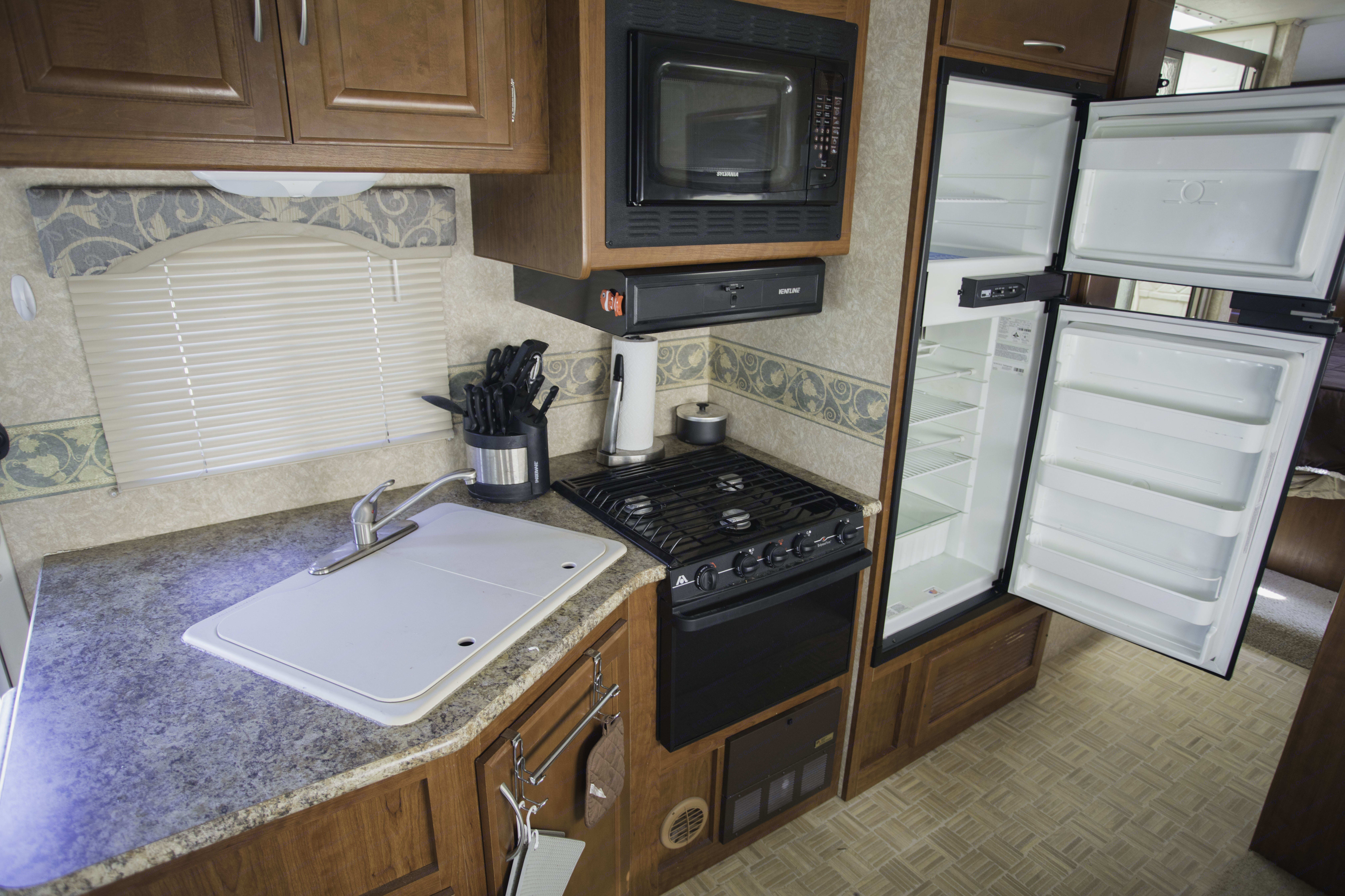 Main kitchen area showing full sized refrigerator and freezer. Microwave above stove with powered exhaust vent.  Dual sinks with hard plastic covers. The dining table is just to the right and out of view in this image.. Thor Motor Coach Four Winds 2009