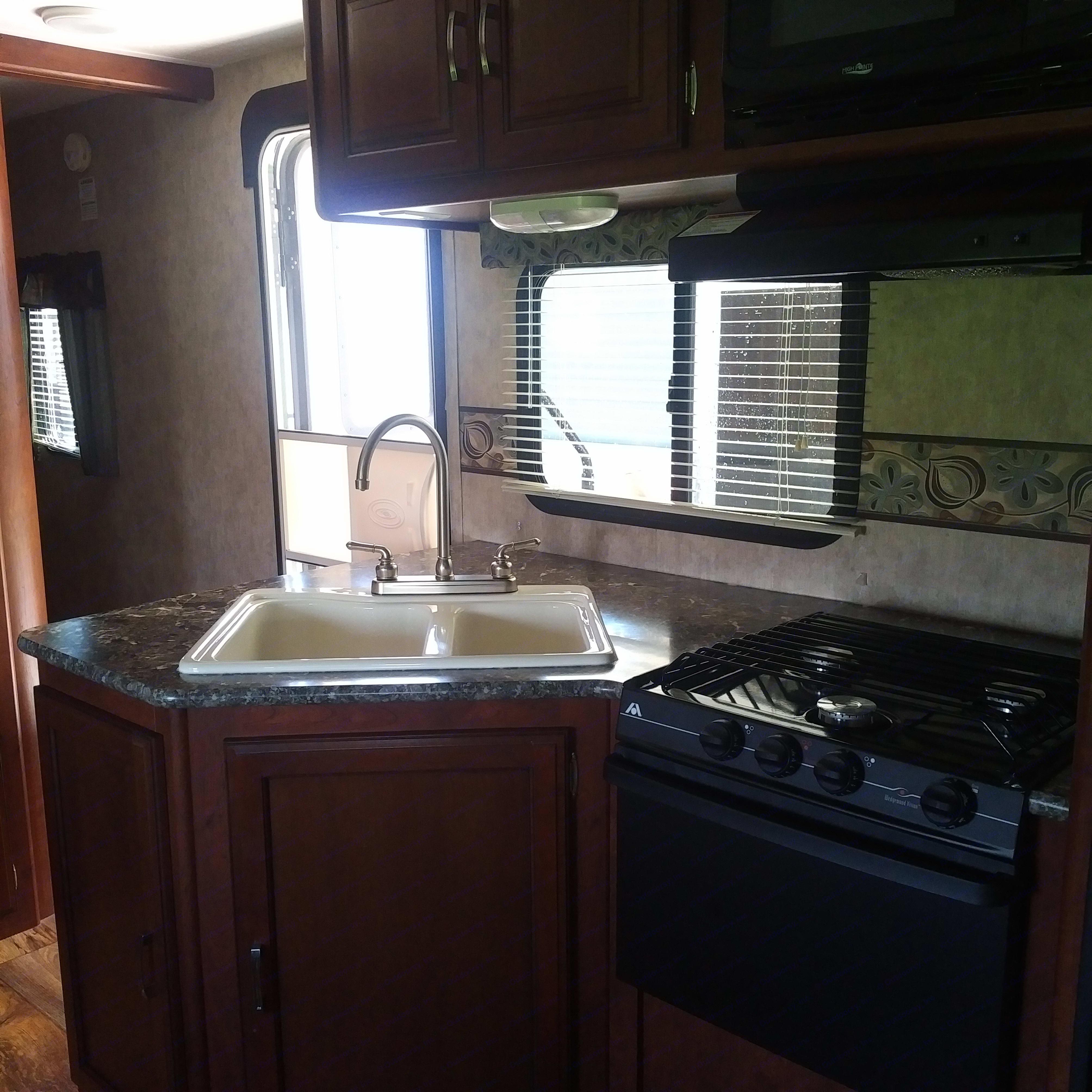kitchen has dbl sink, stove, oven, microwave, larger fridge and freezer. Keystone Passport 2015