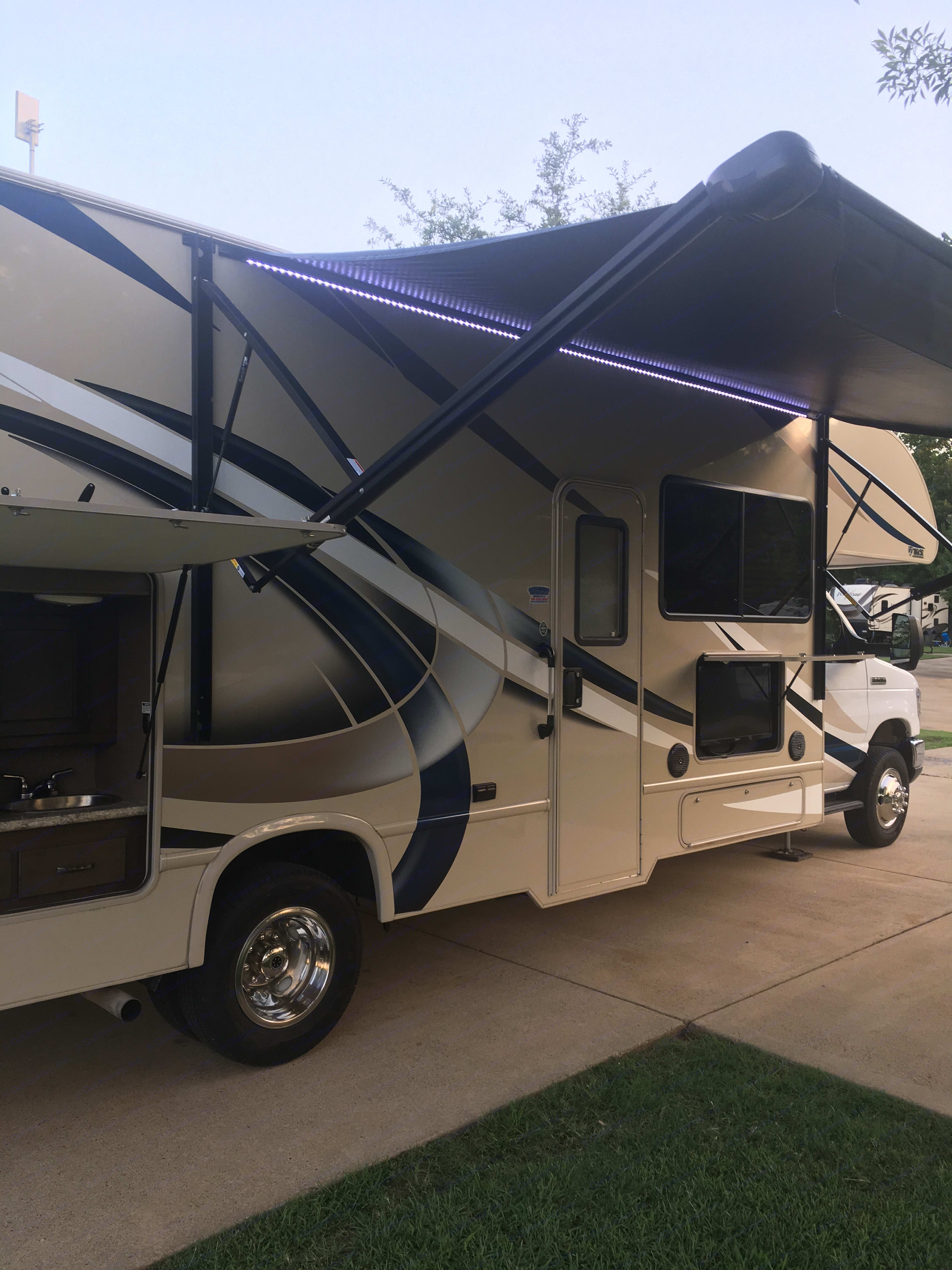 Outside view of awning, LED lights, outdoor TV/radio, Fridge, and sink. Ford Fourwinds 2018