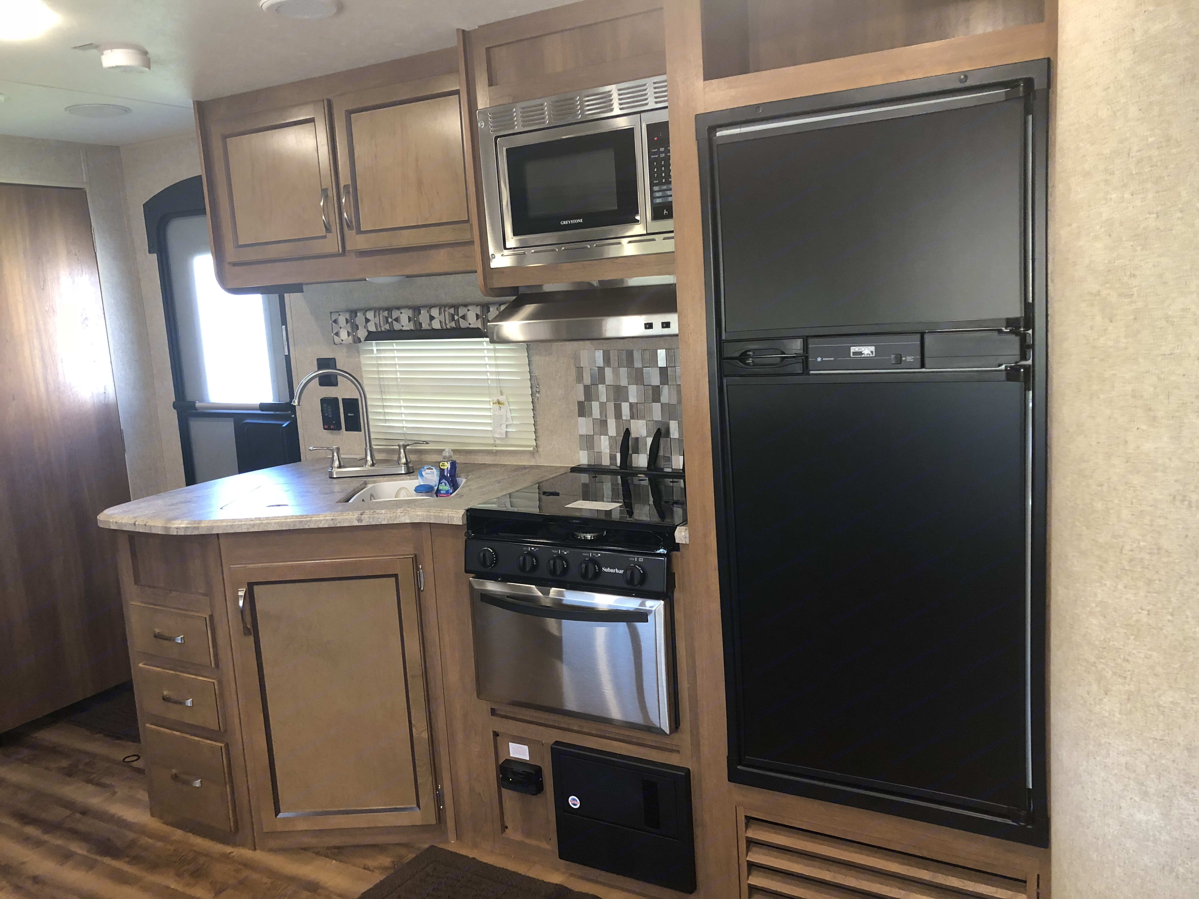 Kitchen with stove, refrigerator, 3 burning stove and double sink. Coachmen Catalina Legacy 2018