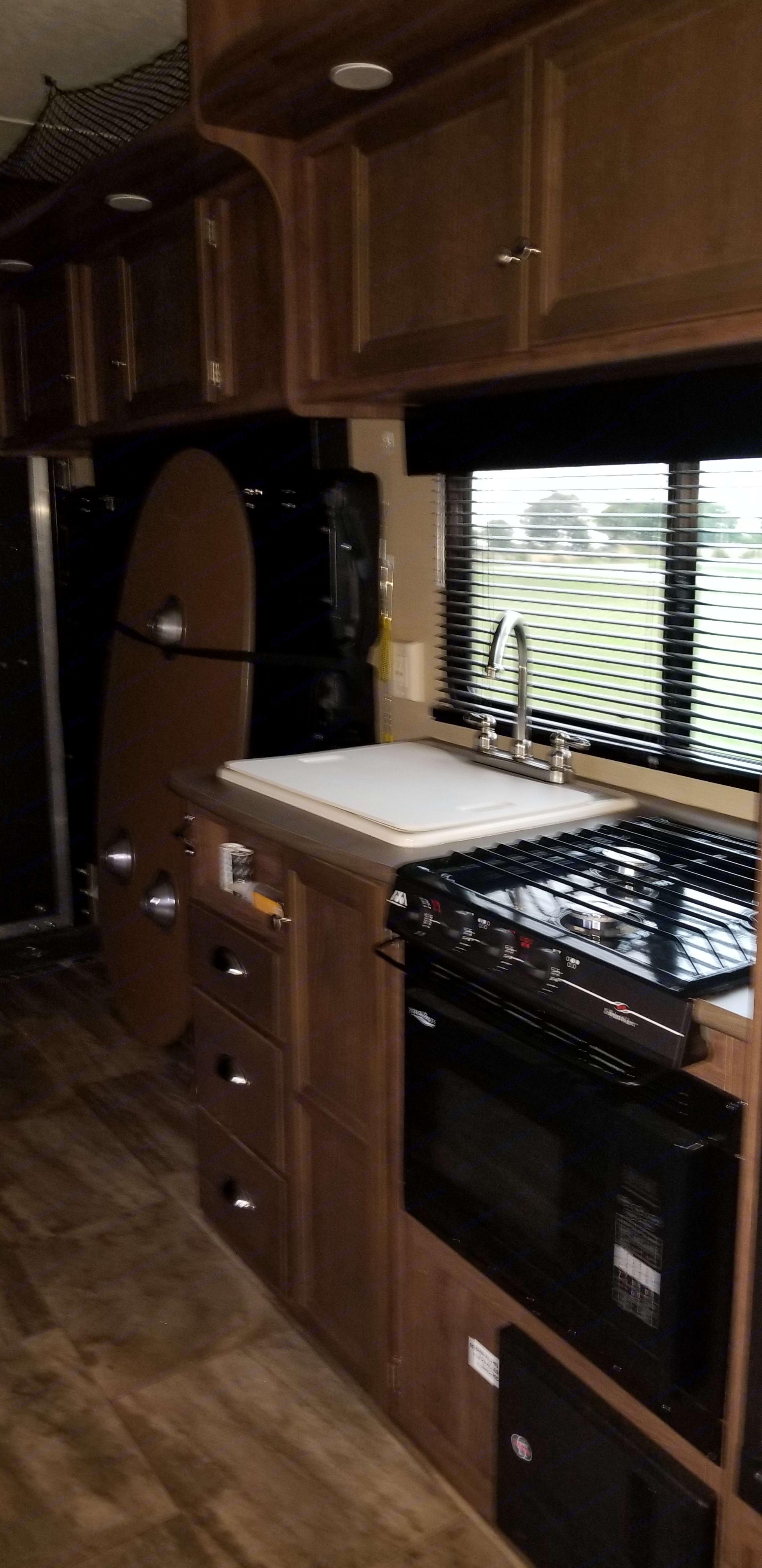 Kitchen. Sink, stove, microwave. Dutchmen Rubicon 2015